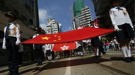 Participants hold a Chinese national flag and a Hong Kong flag as tens of thousands of people march on a down town street to oppose a planned civil disobedience campaign by pro-democracy activists in Hong Kong, Sunday, Aug. 17, 2014. The rally was organized by a pro-Beijing group. Many carried banners or shouted slogans saying they were opposed to the Occupy Central pro-democracy movement