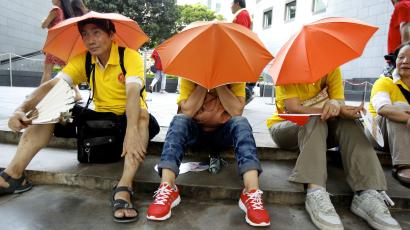 Pro-Beijing protesters rest after taking part in a march to demonstrate against a pro-democracy Occupy Central campaign in Hong Kong August 17, 2014.
