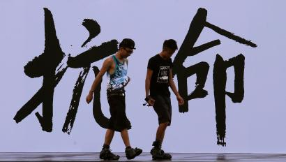 "Pro-democracy activists walk past a backdrop with Chinese characters that read ""disobedience"", built for an Occupy Central civil disobedience campaign, near the financial Central district in Hong Kong August 31, 2014. Hong Kong is poised for a showdown with China when the Chinese parliament met on Sunday, with the largely rubber-stamp body likely to snuff out hopes for a democratic breakthrough in the regional financial hub at elections due in 2017. REUTERS/Bobby Yip (CHINA - Tags: POLITICS) - RTR44DP1"