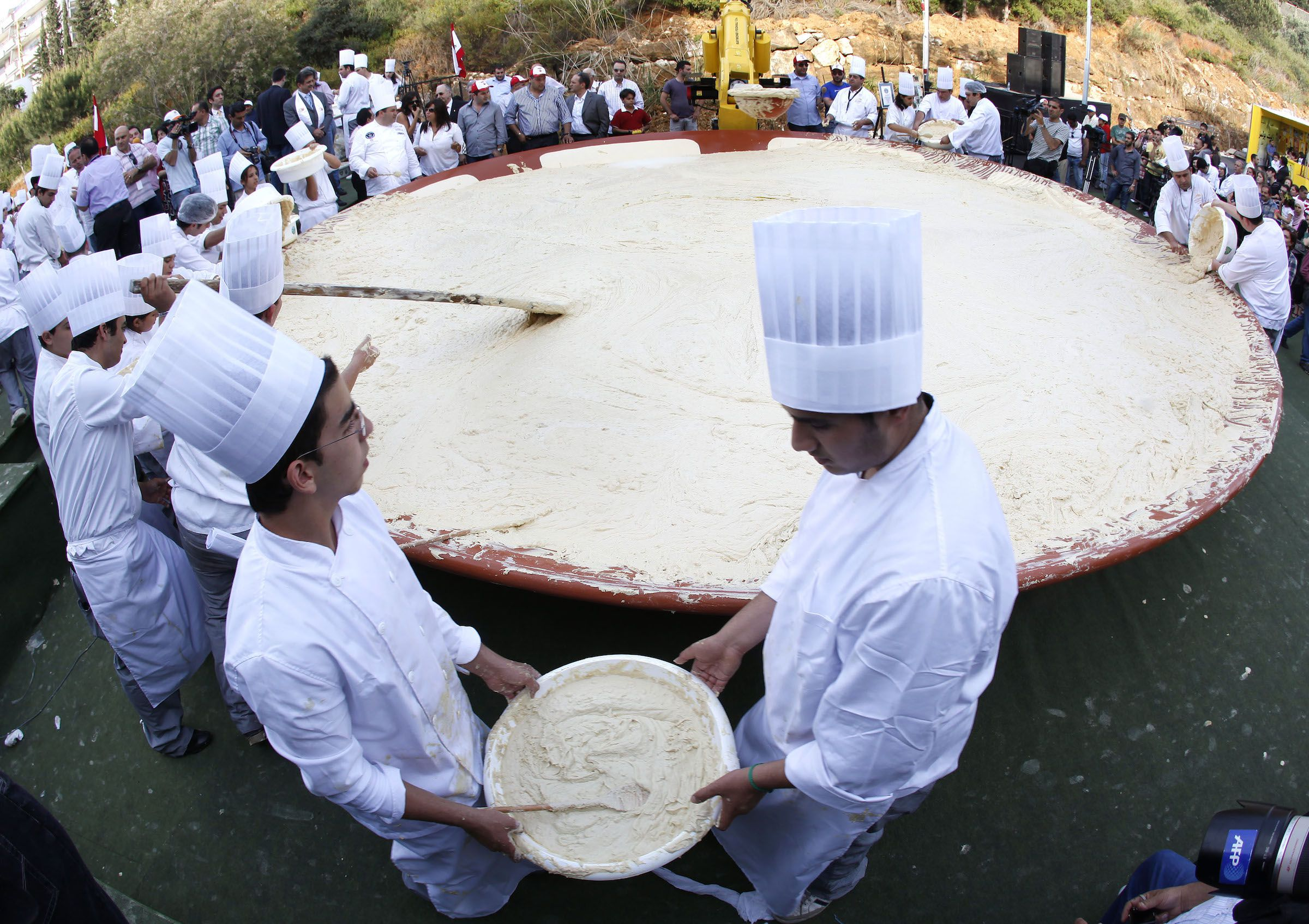 Lebanese chefs prepare a massive bowl of hummus, weighing 22,046 pounds or 10,452 kilograms the size of Lebanon in square kilometers, during a bid to break a record previously held by Israel and reclaim ownership over the popular Middle Eastern dish, in Fanar, east of Beirut, Lebanon, Saturday May 8, 2010. Some 300 Lebanese chefs prepared the huge hummus plate and doubled the record achieved by cooks in an Arab town near Jerusalem in January that weighed around four metric tons and broke a previous record held by Lebanon. A Guinness World Records adjudicator confirmed that Lebanon now holds the record.