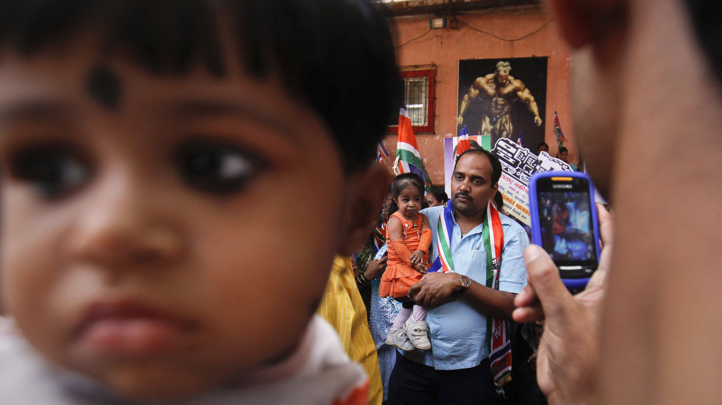 A man takes a picture of Jyoti Amge, the world's shortest living woman, as she is carried by a supporter of local political party Maharashtra Navnirman Sena (MNS) as she campaigns for the upcoming municipal elections in Mumbai December 7, 2012. Amge has been certified by the Guinness World Records as the shortest woman in the world with an average measurement of 24.39 inches (61.95 cm). REUTERS/Danish Siddiqui (INDIA - Tags: SOCIETY POLITICS ELECTIONS)