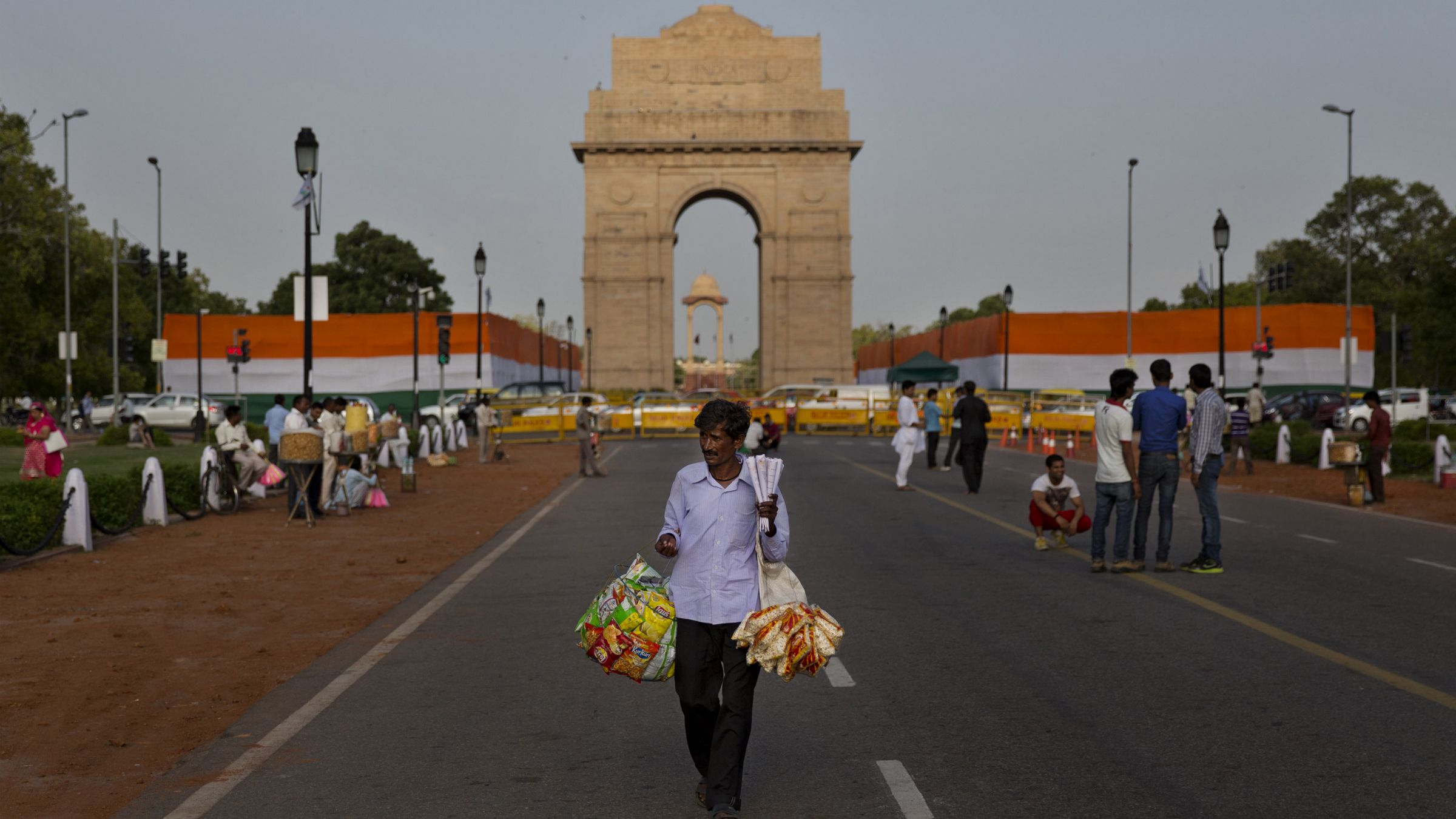 An Indian vendor sells snacks in front of the landmark India Gate war memorial, decorated in the colors of the Indian national flag, on the eve of the country's Independence Day in New Delhi, India, Thursday, Aug. 14, 2014. India celebrates its 1947 independence from British colonial rule on Aug. 15.