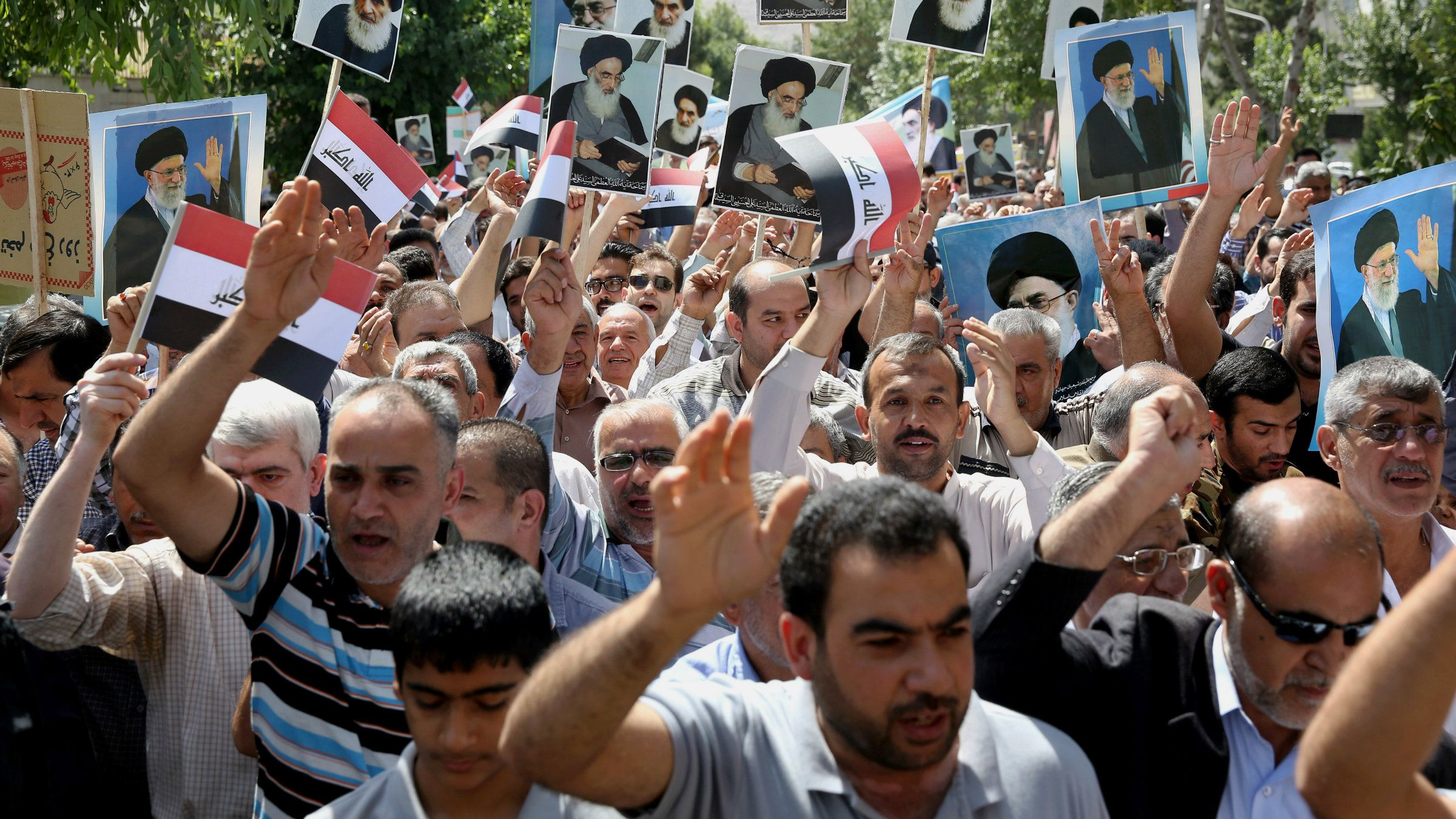 Iraqis living in Iran hold a demonstration against Sunni militants of the al-Qaida-inspired Islamic State of Iraq and the Levant, or ISIL, and to support the Grand Ayatollah Ali al-Sistani, Iraq's top Shiite cleric, shown in the posters, as some of them hold posters of the Iranian Supreme Leader Ayatollah Ali Khamenei, in Tehran, Iran, Friday, June 20, 2014.