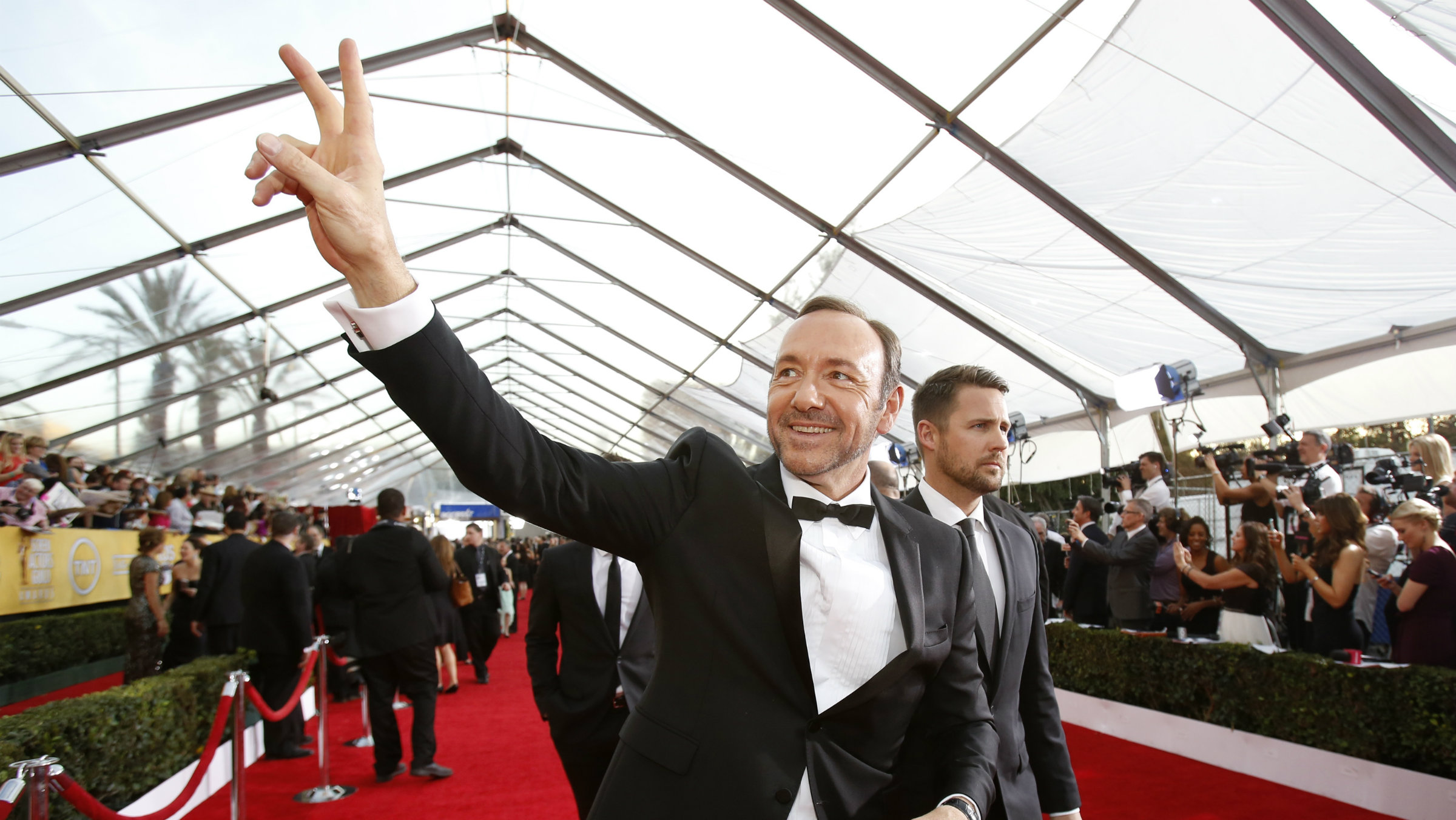 """Actor Kevin Spacey walks the red carpet flashing a """"v"""" sign for victory."""