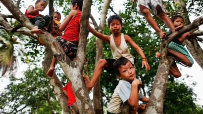 Children climb a tree at a camp for internally displaced persons in the suburbs of Myitkyina