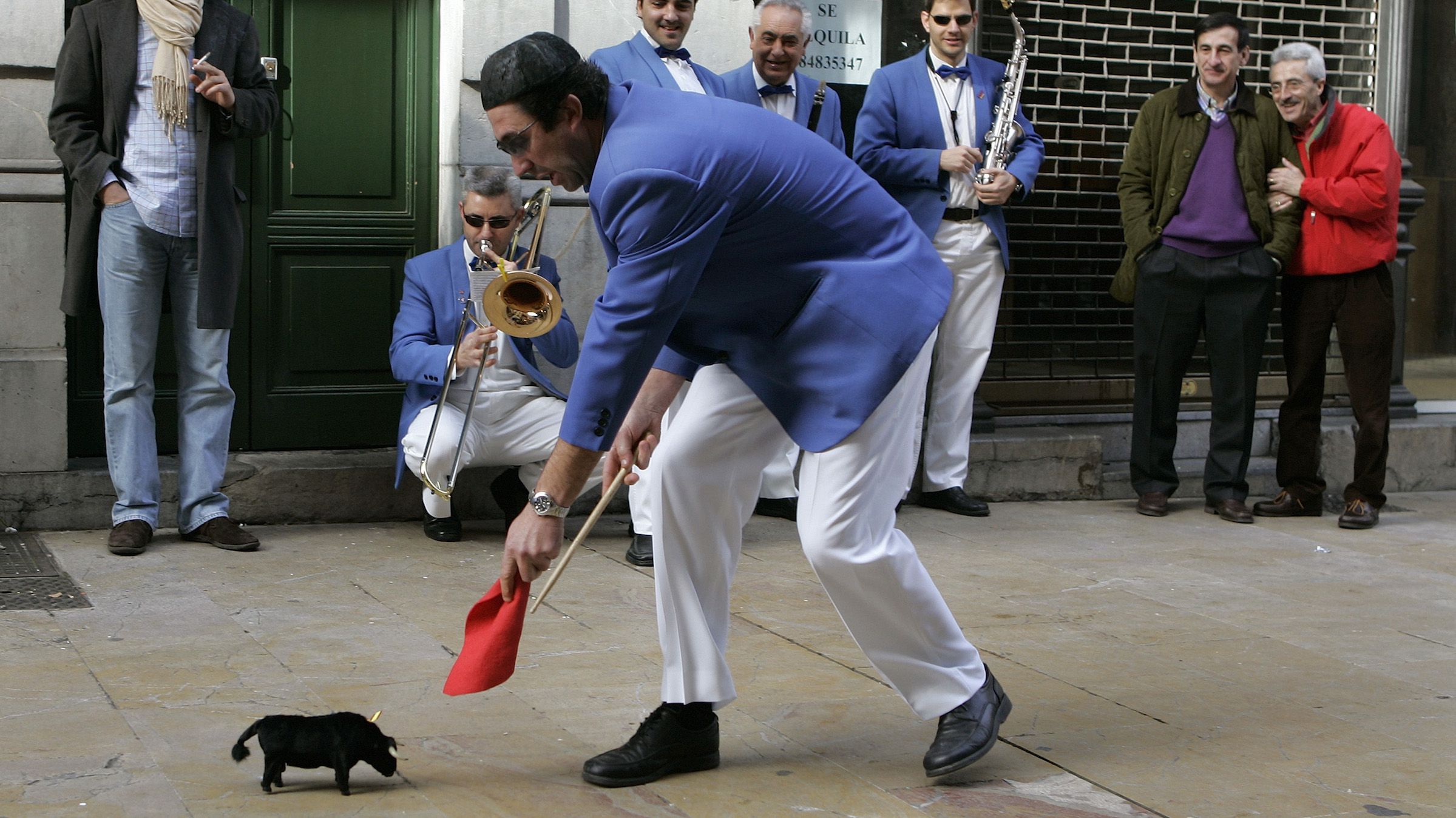 """A member of a carnival """"comparsa"""", also known as carnival musical group, plays with a toy bull in a street of the northern Spanish town of Aviles February 5, 2008. REUTERS/Eloy Alonso (SPAIN) - RTR1WPL1"""