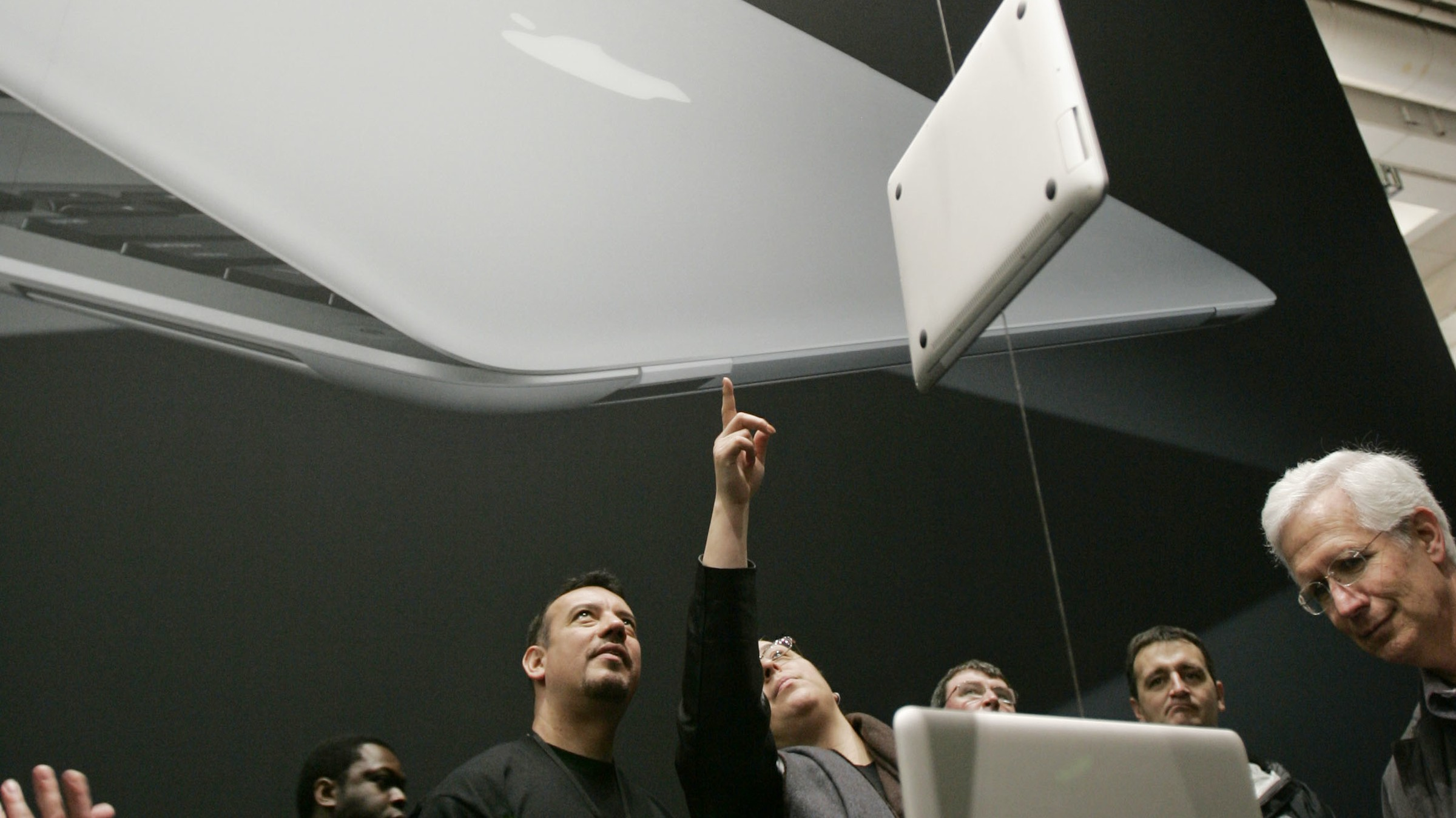 Attendees look at a MacBook Air display at the MacWorld Conference in San Francisco, Tuesday, Jan. 15, 2008. The super-slim new laptop is less than an inch thick and turns on the moment it's opened. (AP Photo/Paul Sakuma)