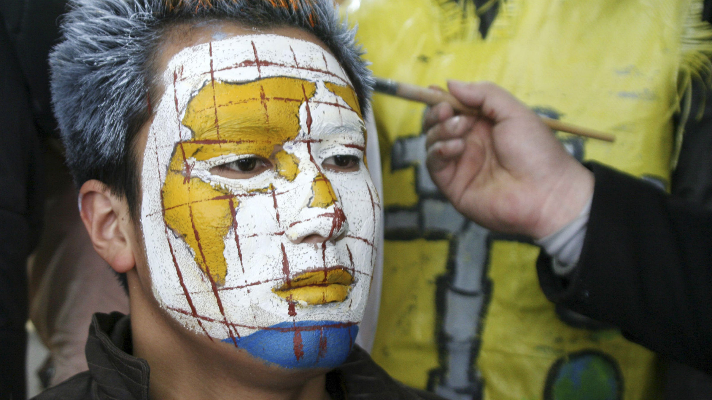"""A student gets a face painting called """"Thirsty Human"""" from his classmate during a campaign to mark the upcoming World Water Day at a vocational education school in Hanshan county, Anhui province, March 21, 2011. The yellow areas on the map in his face painting indicates dry places. March 22 is World Water Day."""
