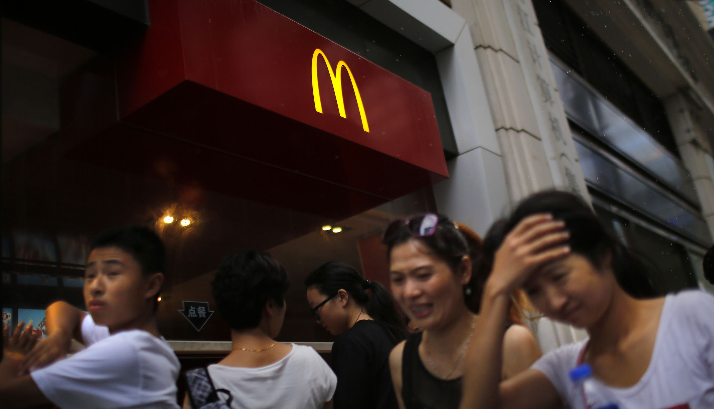"""People walk by a McDonald's store in downtown Shanghai July 31, 2014. A food safety scare in China is testing local consumers' loyalty to foreign fast-food brands, including McDonald's Corp and Yum Brands Inc, which owns the KFC and Pizza Hut chains. Yum said on Wednesday that the scare, triggered by a TV report earlier this month showing improper meat handling by a supplier, Shanghai Husi Food, caused """"significant, negative"""" damage to sales at KFC and Pizza Hut restaurants over the past 10 days. """"If the significant sales impact is sustained, it will have a material effect on full-year earnings per share,"""" Yum said in a regulatory filing.  REUTERS/ Carlos Barria  (CHINA - Tags: BUSINESS FOOD HEALTH) - RTR40RF0"""