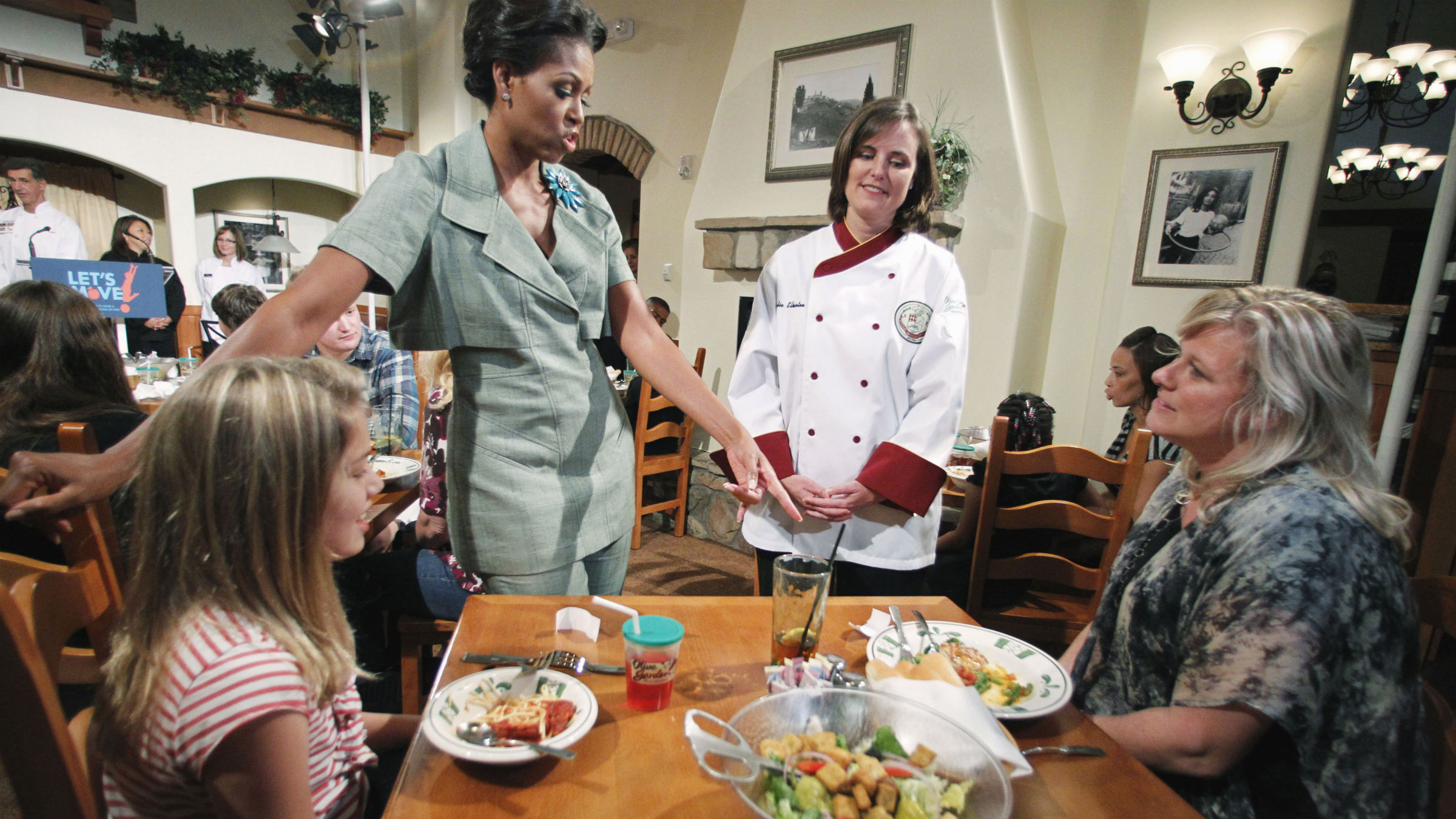 First Lady Michelle Obama, accompanied by Darden chef Julie Elkinton, second from right, talks to Charisse McElroy, right, and her daughter Jacqueline McElroy, 9, during a Let's Move! event in one of Darden's national restaurants in Hyattsville, Md., Thursday, Sept. 15, 2011. The first lady announced Darden Restaurants' commitment to reduce its calorie and sodium footprint and to provide greater choice and variety on its children's menus and make healthy options the default choice whenever possible.