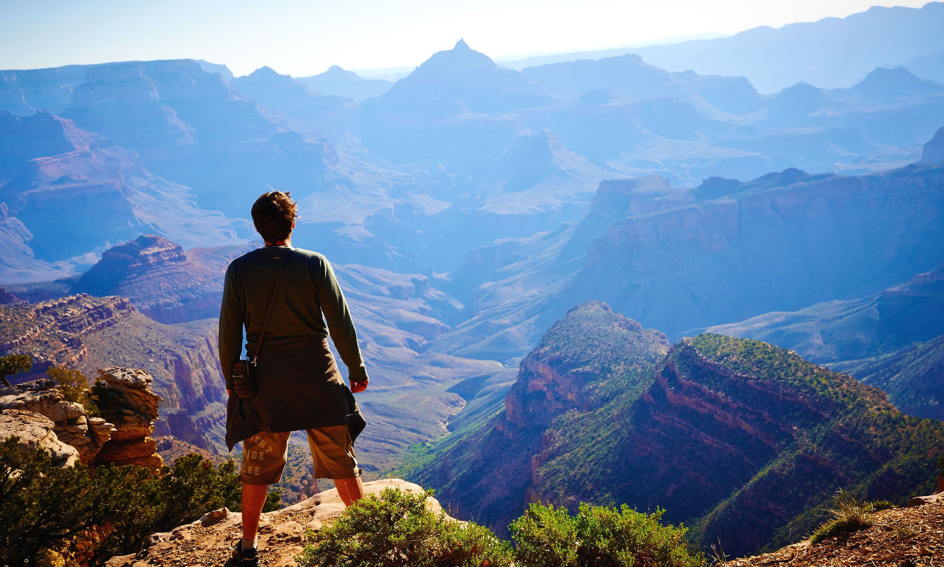 a hiker watches sunrise over the Grand Canyon