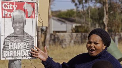 A woman reacts as she see a newspaper poster with a photo of former South African President Nelson Mandela on it in Mthatha, South Africa