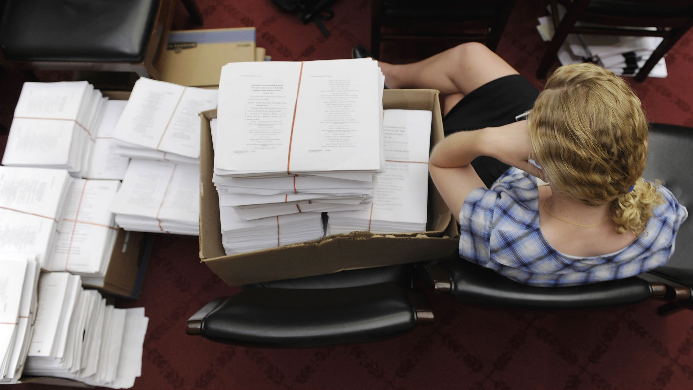 "An intern for House Energy and Commerce Committee Chairman Henry Waxman (D-CA) sits with stacks of paperwork in anticipation of a committee meeting to mark-up health care legislation titled ""America's Affordable Health Choices Act of 2009,"" on Capitol Hill in Washington, July 29, 2009."