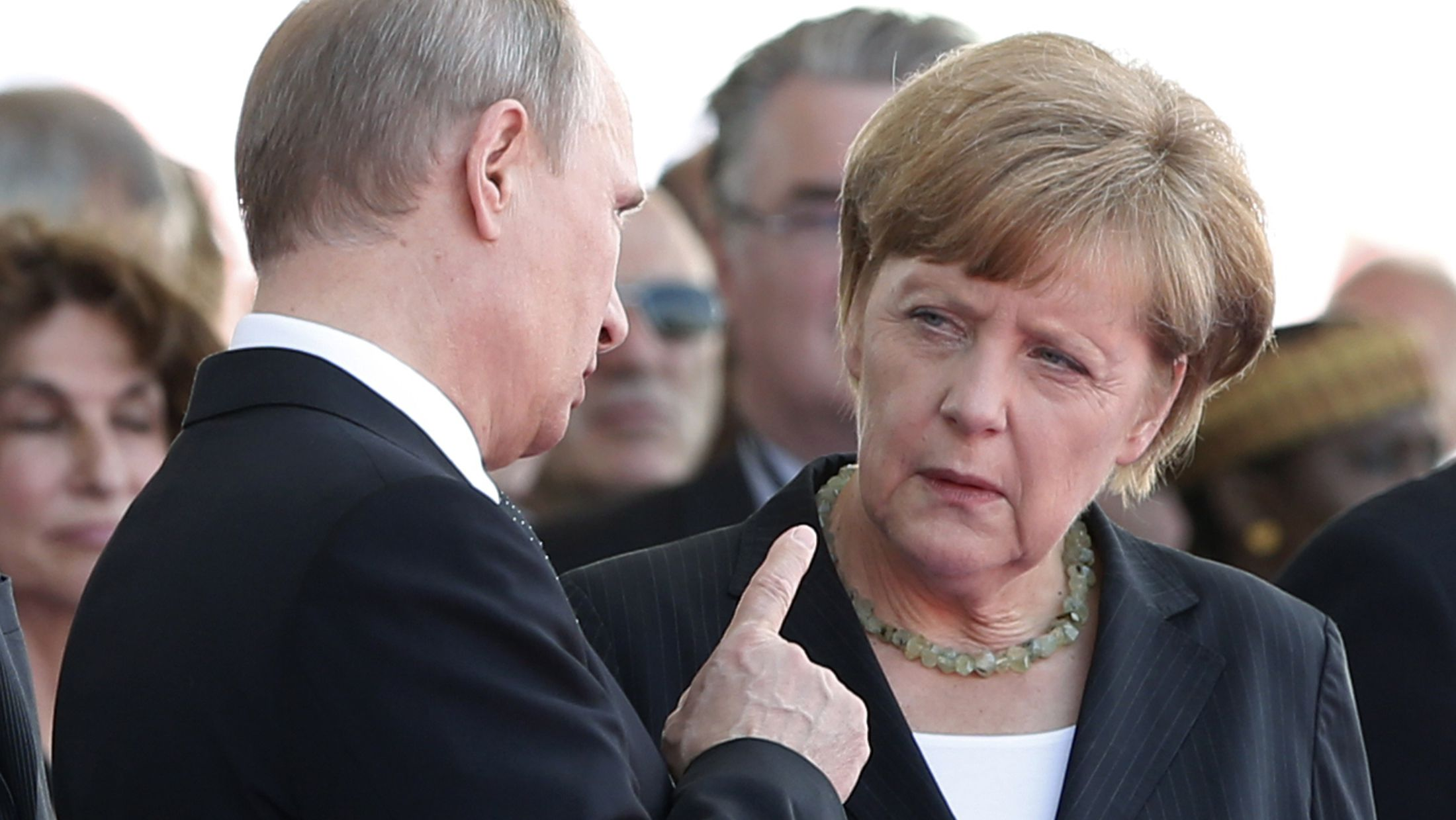 Russian President Vladimir Putin talks with German Chancellor Angela Merkel as they attend the International 70th D-Day Commemoration Ceremony in Ouistreham June 6, 2014. World leaders and veterans gathered by the beaches of Normandy on Friday to mark the 70th anniversary of the Allied D-Day landings that helped turn the tables in World War Two, with host France hoping the event will bring a thaw in the?Ukraine?crisis.