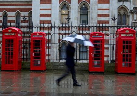 A man shelters under an umbrella as he walks past red telephone boxes in central London April 17, 2012. REUTERS/Olivia Harris (BRITAIN - Tags: CITYSPACE SOCIETY BUSINESS TELECOMS) - RTR30UWV
