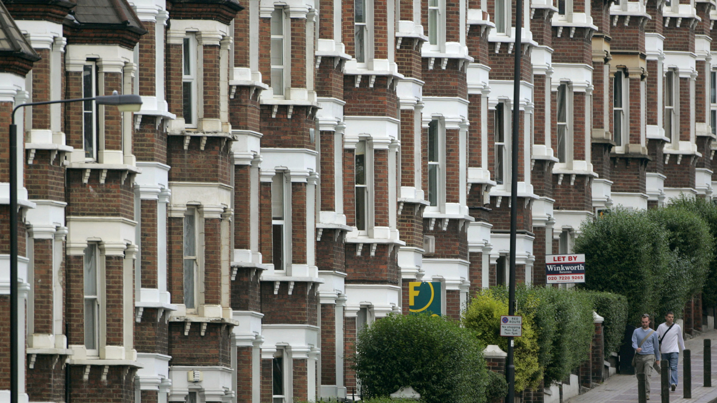 People walk past estate agents' signs outside a row of houses along a street in south London.