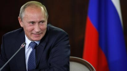 Vladimir Putin smiles while chairing a meeting in Moscow.