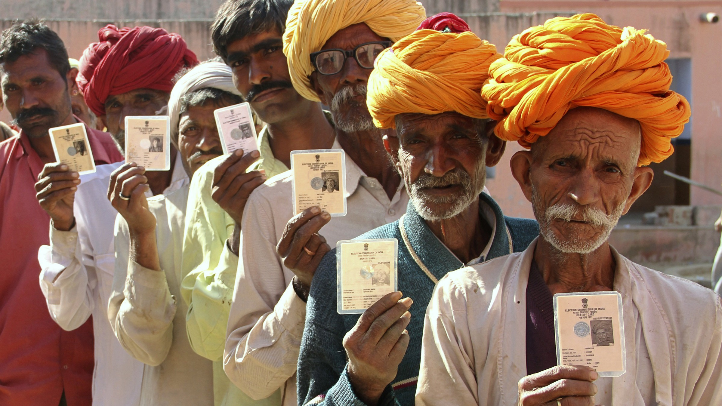 Villagers pose with their identity cards as they stand in line to open a bank account at a camp organised by a private bank in a village at Ajmer in the desert Indian state of Rajasthan, January 10, 2013. New Delhi plans to directly transfer cash payments for subsidies into these accounts, a move aimed at tackling graft in India's creaky, corruption-ridden public distribution system. If successful, the initiative could also bring modern banking to the doorstep of rural India, a goal towards which progress has so far been fitful despite mandatory targets set by the government and Reserve Bank of India. Picture taken January 10, 2013. To match Feature INDIA-RURAL/BANKS REUTERS/Stringer (INDIA - Tags: POLITICS SOCIETY POVERTY BUSINESS) - RTR3CPLC