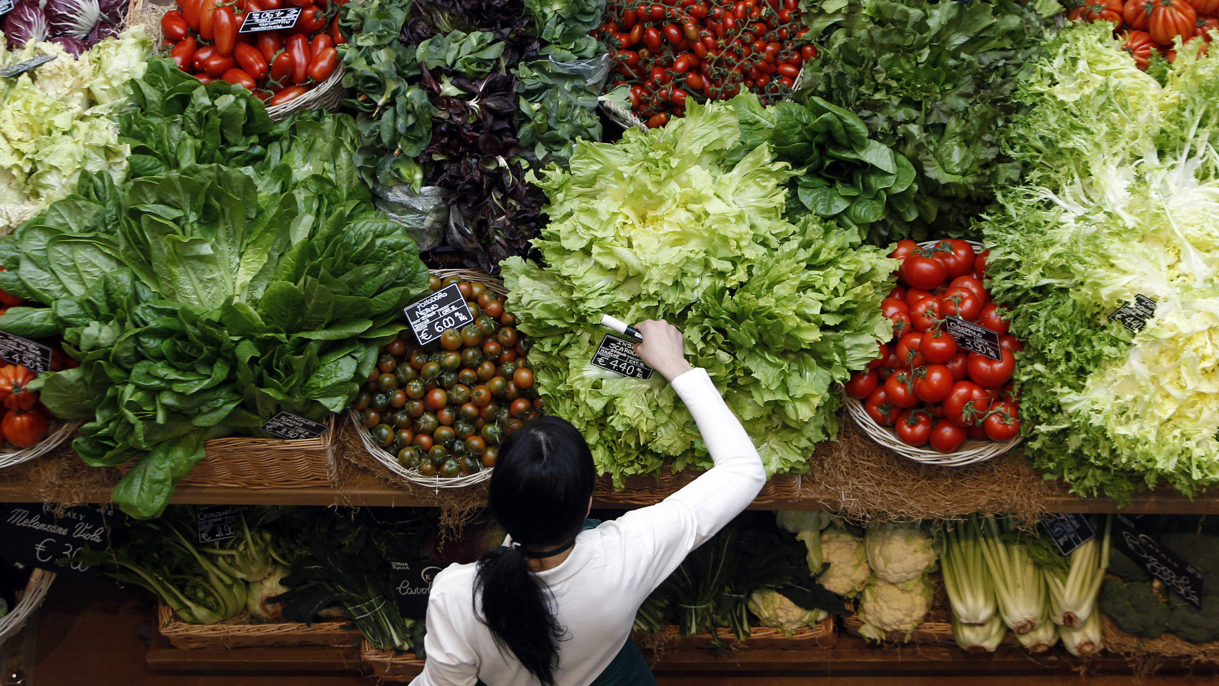 An employee arranges pricetags at a vegetables work bench during the opening day of upmarket Italian food hall chain Eataly's flagship store in downtown Milan.