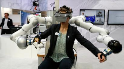 A woman uses a HUG, (Haptic User Geraet), during the 6th International Trade Fair for Automation and Mechatronics in Munich June 5, 2014. HUG is the bimanual haptic interaction device of the DLR Robotics and Mechatronics Center, designed for training of astronauts and mechanics, rehabilitation and other tasks. REUTERS/Michaela Rehle (GERMANY - Tags: BUSINESS SCIENCE TECHNOLOGY) - RTR3SC12