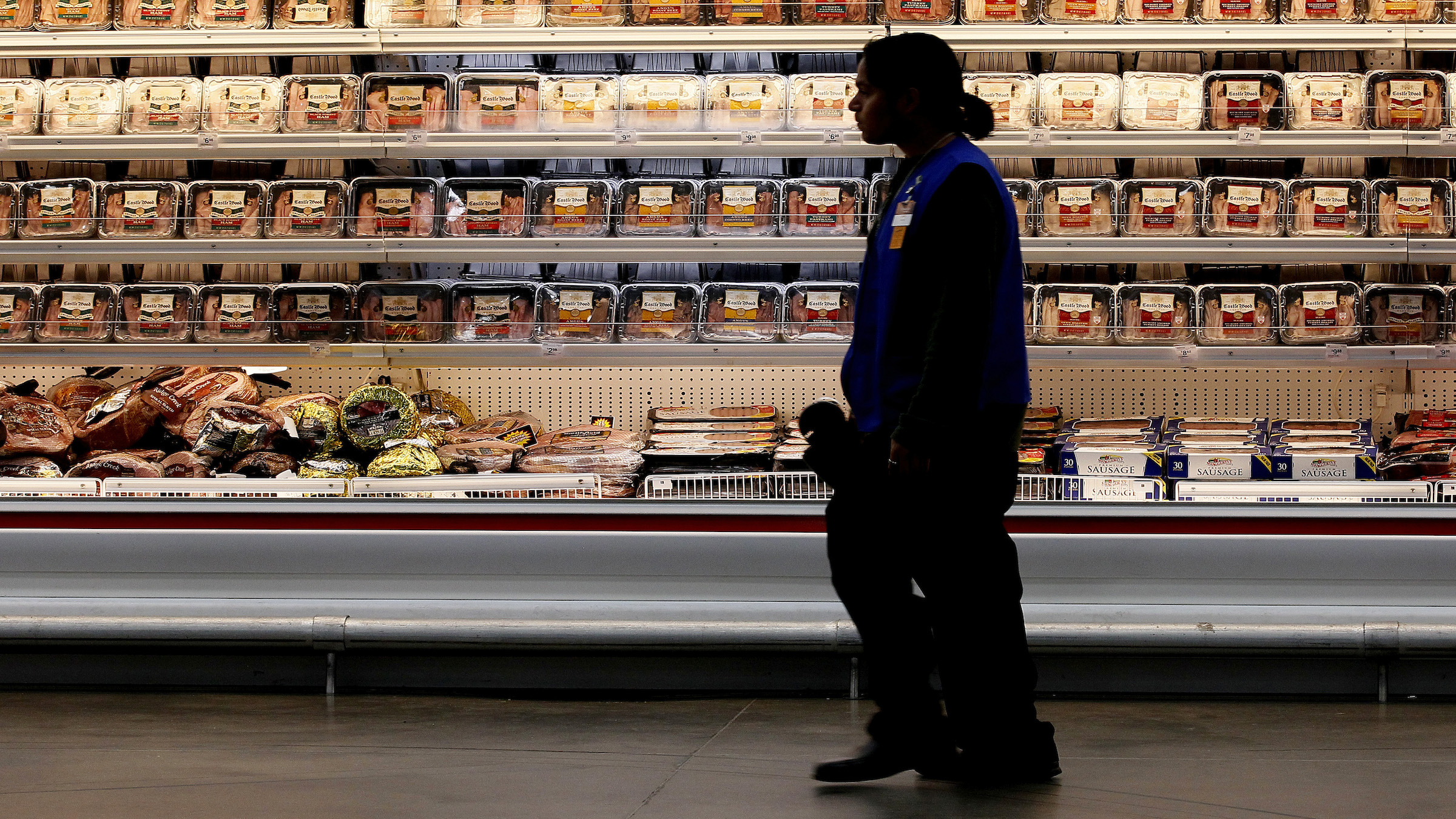 A employee walks by a meat cooler in the grocery section of a Sam's Club during a media tour in Bentonville, Arkansas June 5, 2014.  The tour was part of Walmart Stores Inc. annual shareholder meeting.   REUTERS/Rick Wilking