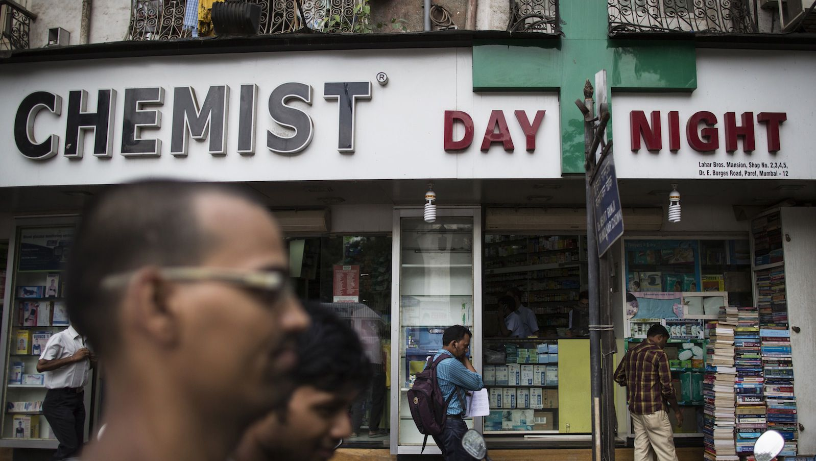 People walk past a chemist shop at a market in Mumbai June 24, 2014. India's health ministry has formed a committee that will meet for the first time on Tuesday to consider raising the number of drugs deemed essential and subject to price caps, people directly involved in the process said. A panel formed by India's health ministry is meeting for the first time on Tuesday to consider adding more drugs to the list of essential medicines, all of which would then come under price caps, one of the people said. The move would make the drugs more affordable in a country where 70 percent of the people live on less than $2 a day. REUTERS/Danish Siddiqui (INDIA - Tags: HEALTH BUSINESS) - RTR3VFYH