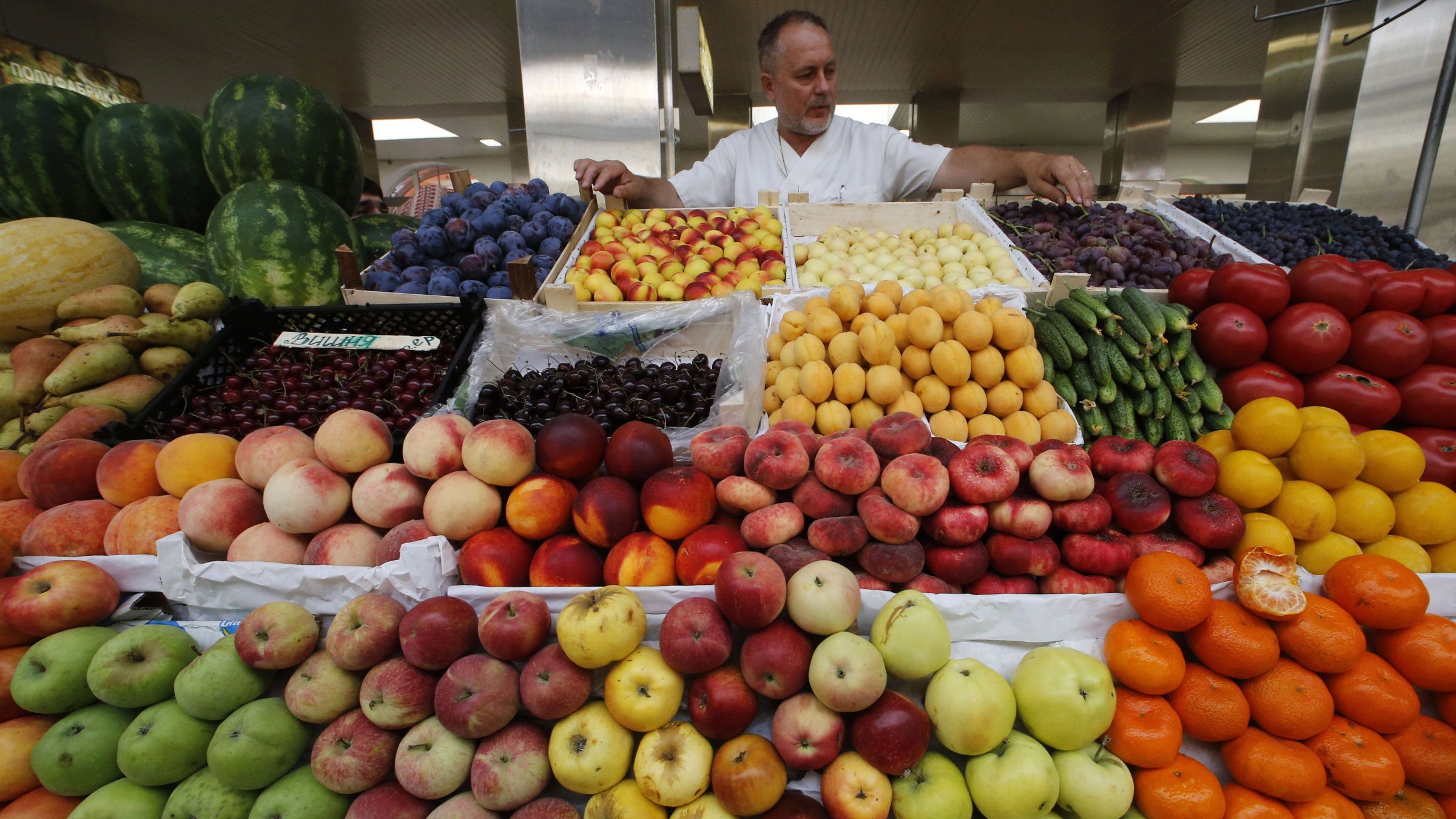 A vendor sells vegetables and fruits at the city market in St. Petersburg.