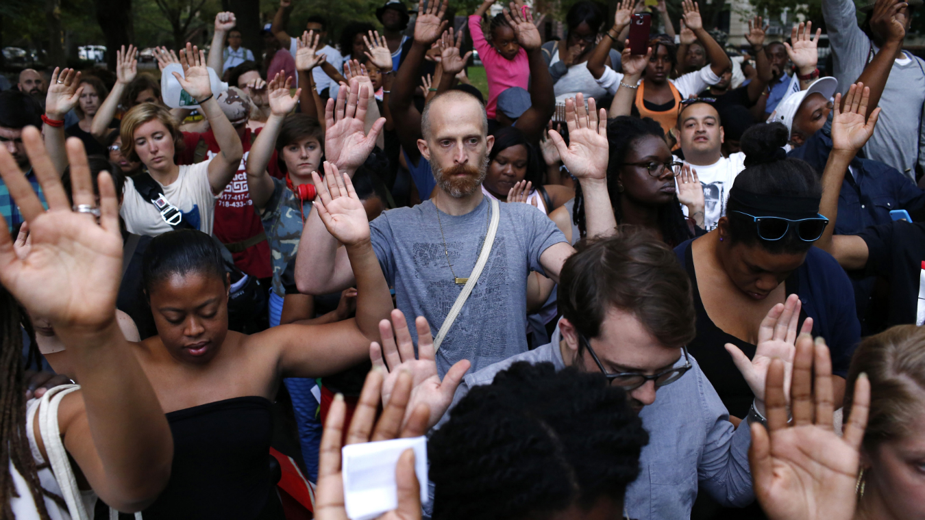 People put their hands up as a symbol to honor Michael Brown, who was shot and killed by an unnamed police officer last Saturday in Ferguson, Missouri, at the borough of Brooklyn in New York August 14, 2014. Reuters/Eduardo Munoz