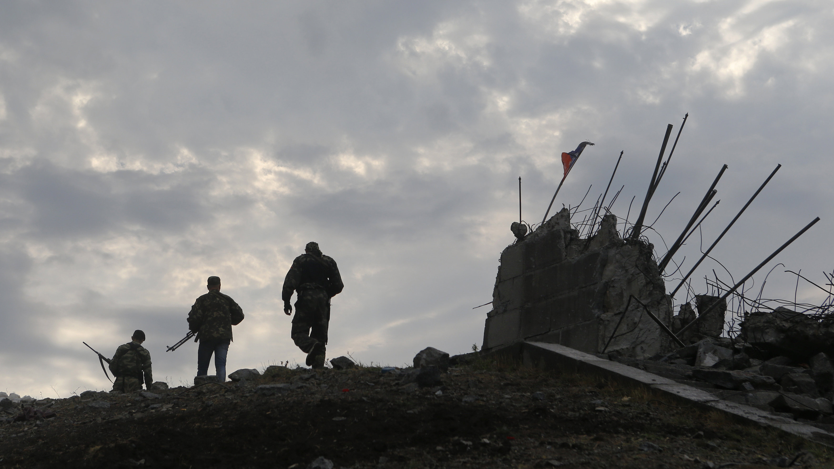 Pro-Russian separatists walk at a destroyed war memorial on Savur-Mohyla, a hill east of the city of Donetsk, August 28, 2014