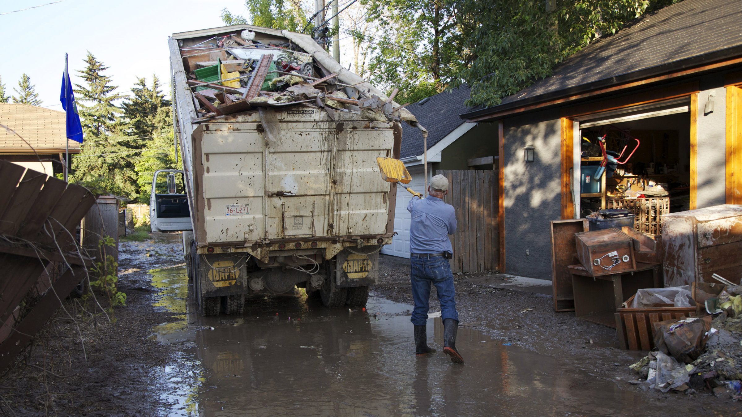A man loads a dump truck with garbage as he clears out his house.