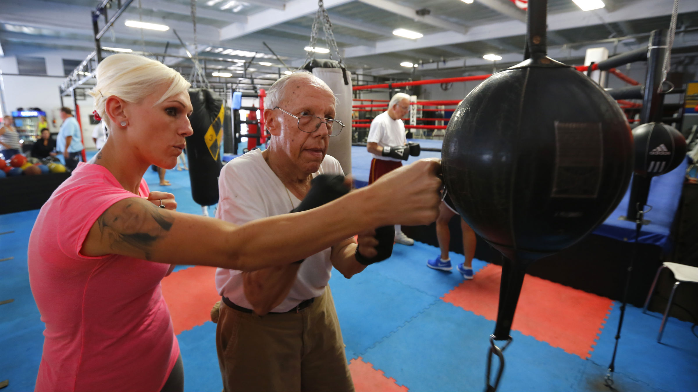 An old man takes a boxing lesson