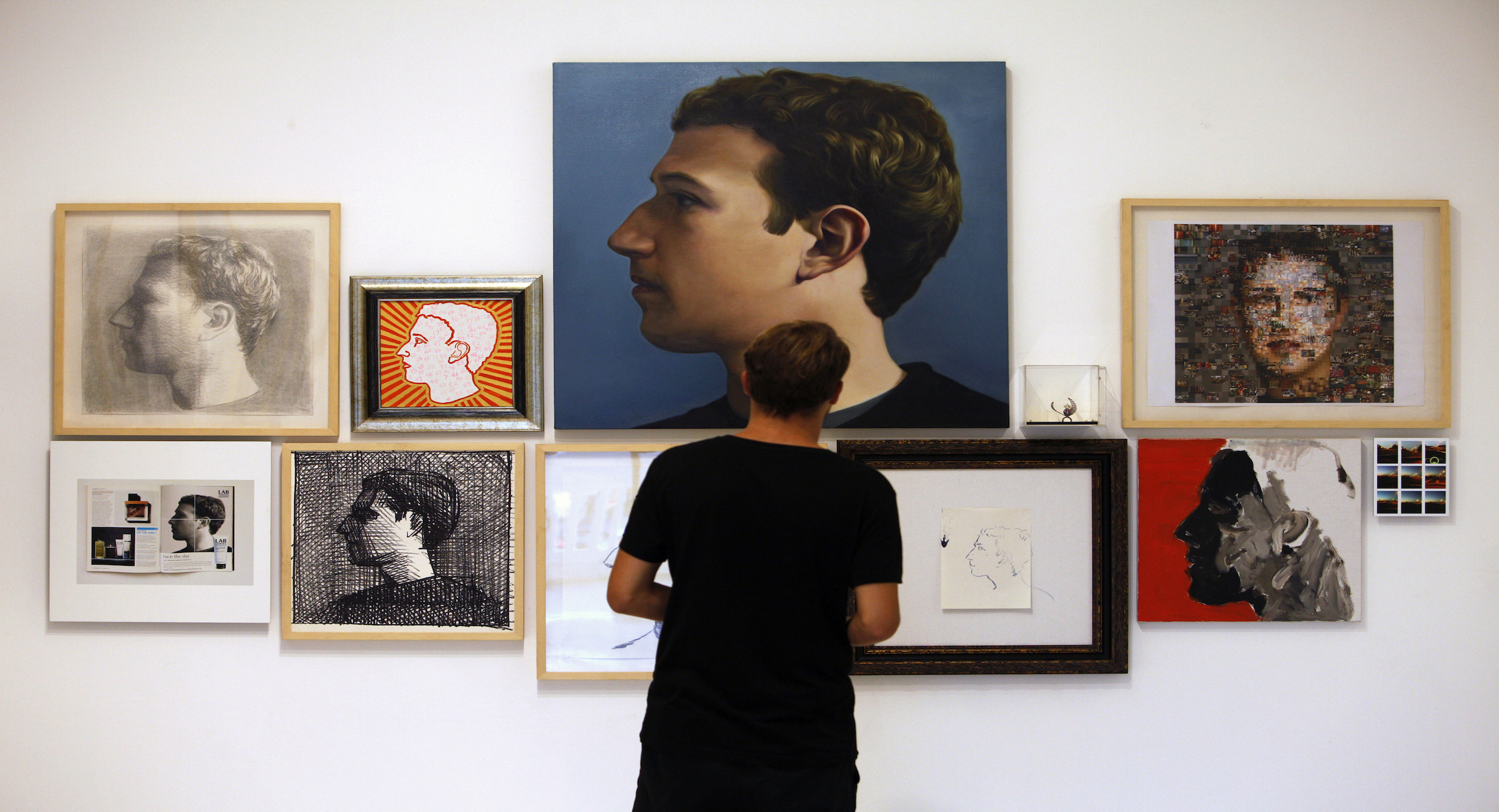 """A visitor looks at portraits of Facebook's founder Mark Zuckerberg at solo exhibition """"The Face of Facebook"""" by Chinese artist Zhu Jia at a gallery in Singapore October 30, 2013. To bring across the potency of social media in this exhibition, Zhu invited over 50 friends of various professions in his personal network, including some of the biggest names in China's contemporary art scene and friends of friends, to re-enact in their own style the iconic image of Zuckerberg featured in a September 2010 issue of the New Yorker article titled """"The Face of Facebook"""". The 67 artworks, in various size and mediums ranging from oil paintings to digital prints, will be sold as a complete collection to a single buyer at the price of S$700,000 ($565,650), according to the gallery. The exhibition runs from October 23 to December 9.  REUTERS/Edgar Su (SINGAPORE - Tags: SOCIETY SCIENCE TECHNOLOGY) - RTX14TT1"""