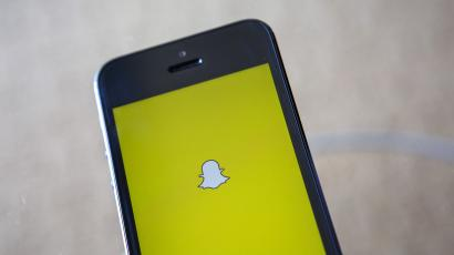 A portrait of the Snapchat logo on a mobile phone.