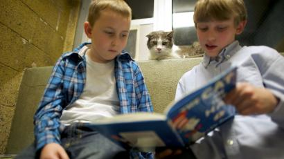 two kids reading with their cat