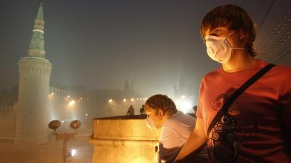 russia climate change global warming forest fire smog People wearing protective masks look at the Moscow Kremlin shrouded in smog, August 4, 2010. Air quality levels in Moscow tumbled to an eight-year low on Wednesday as the Russian capital was blanketed in thick smoke from forest and peat fires, said Moscow's state agency for monitoring air pollution. REUTERS/Sergei Karpukhin