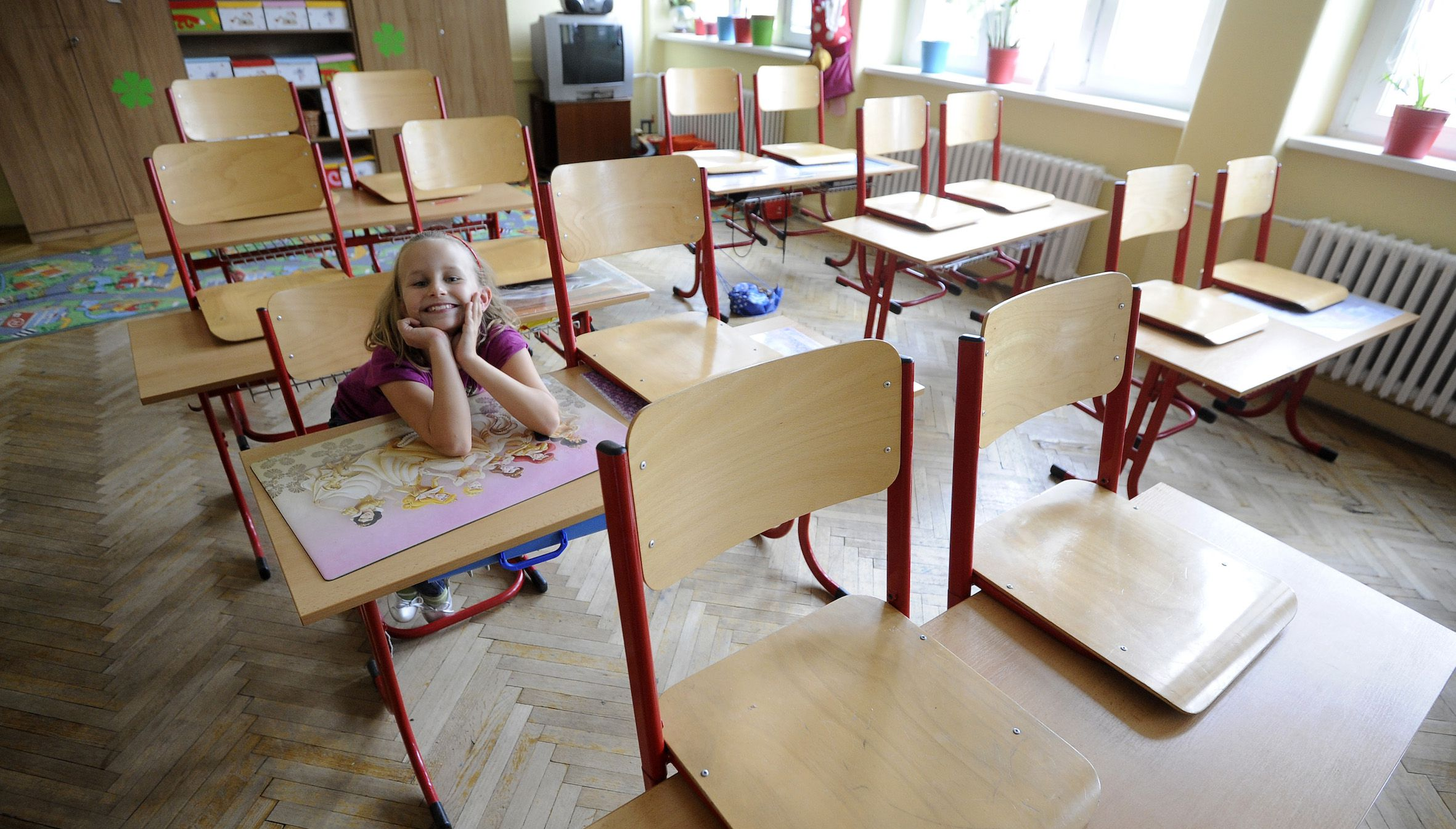 Primary school student Mia (7) smiles inside a classroom in an empty school, closed during a one-day strike by local teachers seeking higher salaries and better work conditions, in Bratislava September 13, 2012. Mia, along with other children whose parents were unable to take care of them during the strike on Wednesday, were placed in the care of volunteers who offered their services to take care of them. REUTERS/Radovan Stoklasa (SLOVAKIA - Tags: EDUCATION CIVIL UNREST BUSINESS EMPLOYMENT) - RTR37WZ5