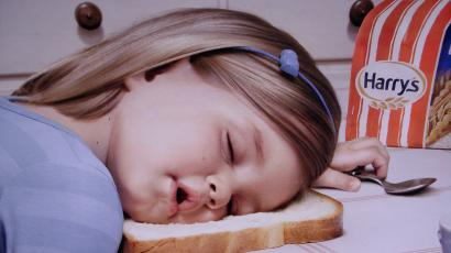 girl sleeping with head on a piece of bread