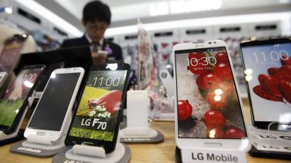 A sales assistant uses his mobile phone in front of mock LG electronics smart phones displayed at a store in Seoul July 22, 2014. South Korea's LG Electronics Inc said on July 24, 2014 its second-quarter profit rose 26.5 percent from a year earlier, beating analyst estimates, as the company's mobile business ran a profit for the first time in four quarters. Picture taken July 22. REUTERS/Kim Hong-Ji (SOUTH KOREA - Tags: BUSINESS TELECOMS)