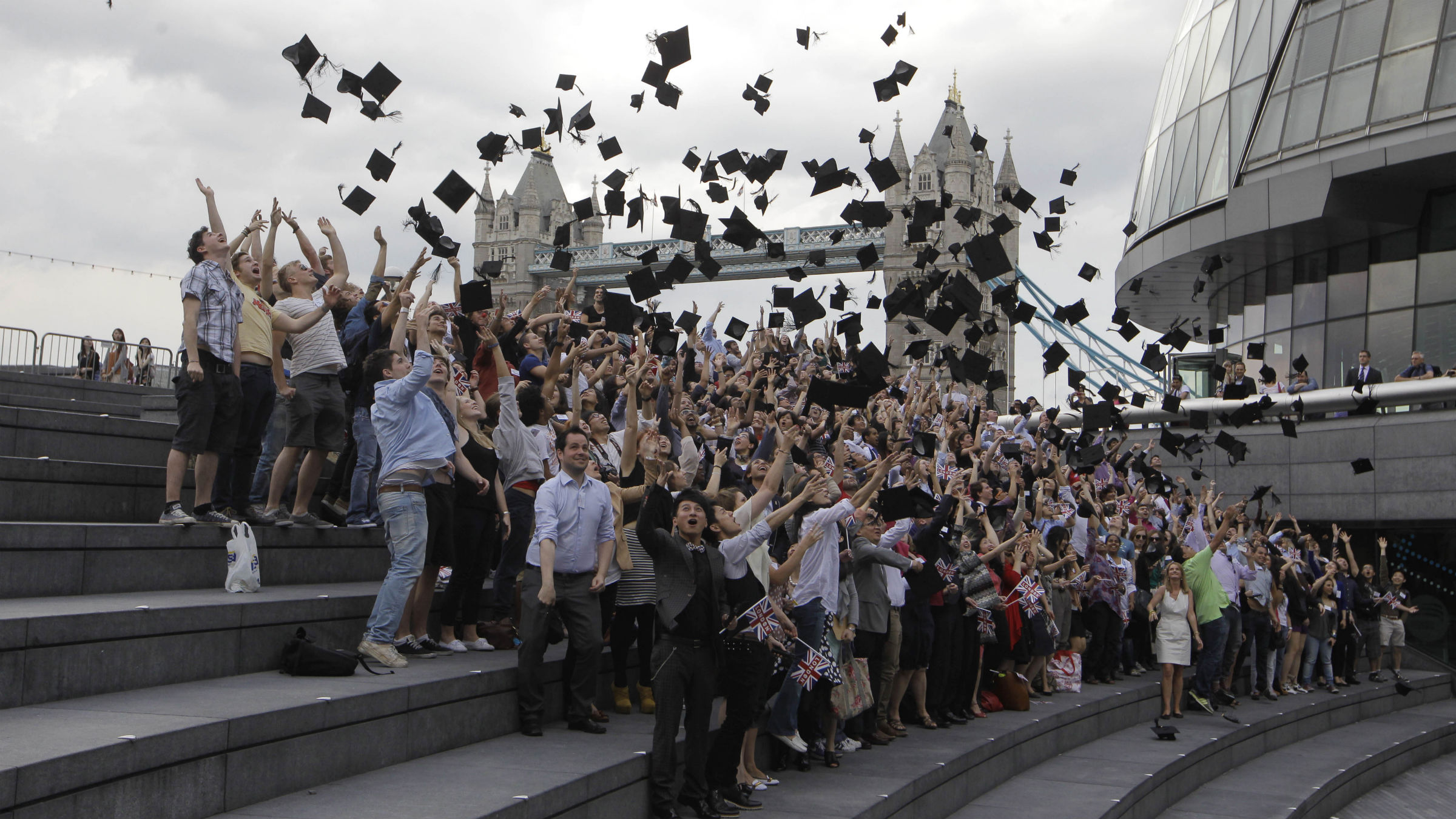 Backdropped by Tower Bridge, hundreds of students from more than 100 nationalities toss their mortar boards into the air in a Guinness World Record attempt for the most people throwing mortar boards simultaneously outside City Hall, right, in London as part of World Record London to mark the news that more international students than ever are now studying in London, Wednesday, May 30, 2012. 295 students took part and set a new Guinness World Record.
