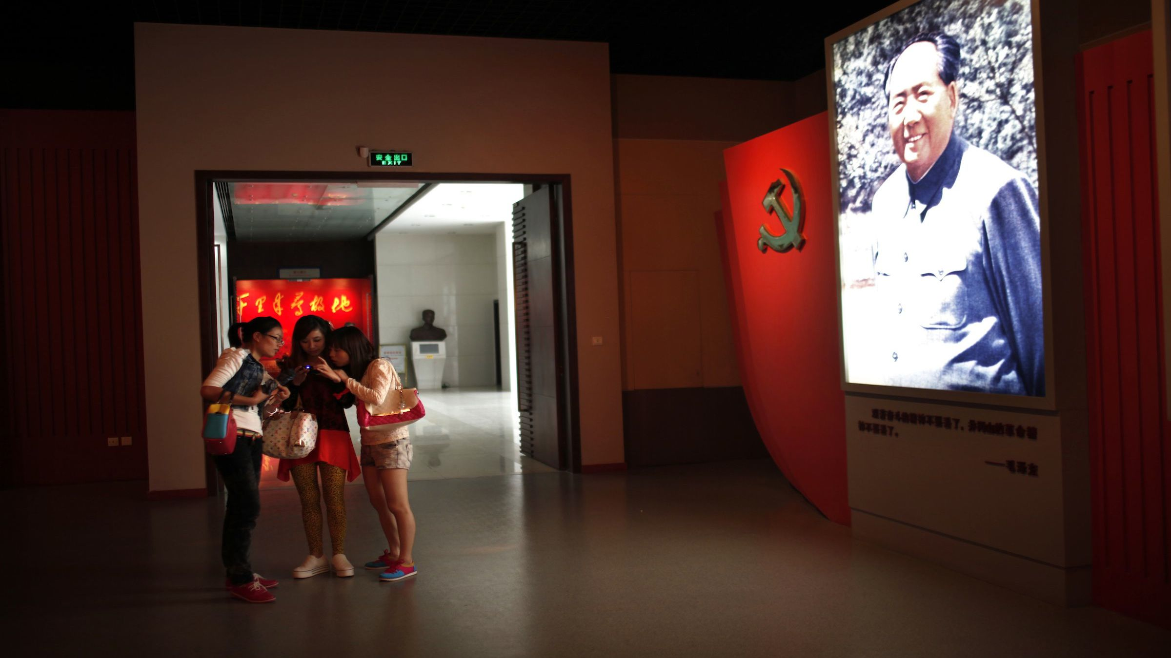 Teenagers looks at the screen of mobile phone as they stand next to a portrait of former Chinese leader Mao Zedong at the Revolution museum in Jinggangshan, Jiangxi province, September 20, 2012. China has yet to announce the start date for the 18th Communist Party Congress, China's biggest political meeting in 10 years, which will see the transfer of power from President Hu Jintao and Premier Wen Jiabao to a new generation. REUTERS/Carlos Barria  (CHINA - Tags: POLITICS) - RTR3873I