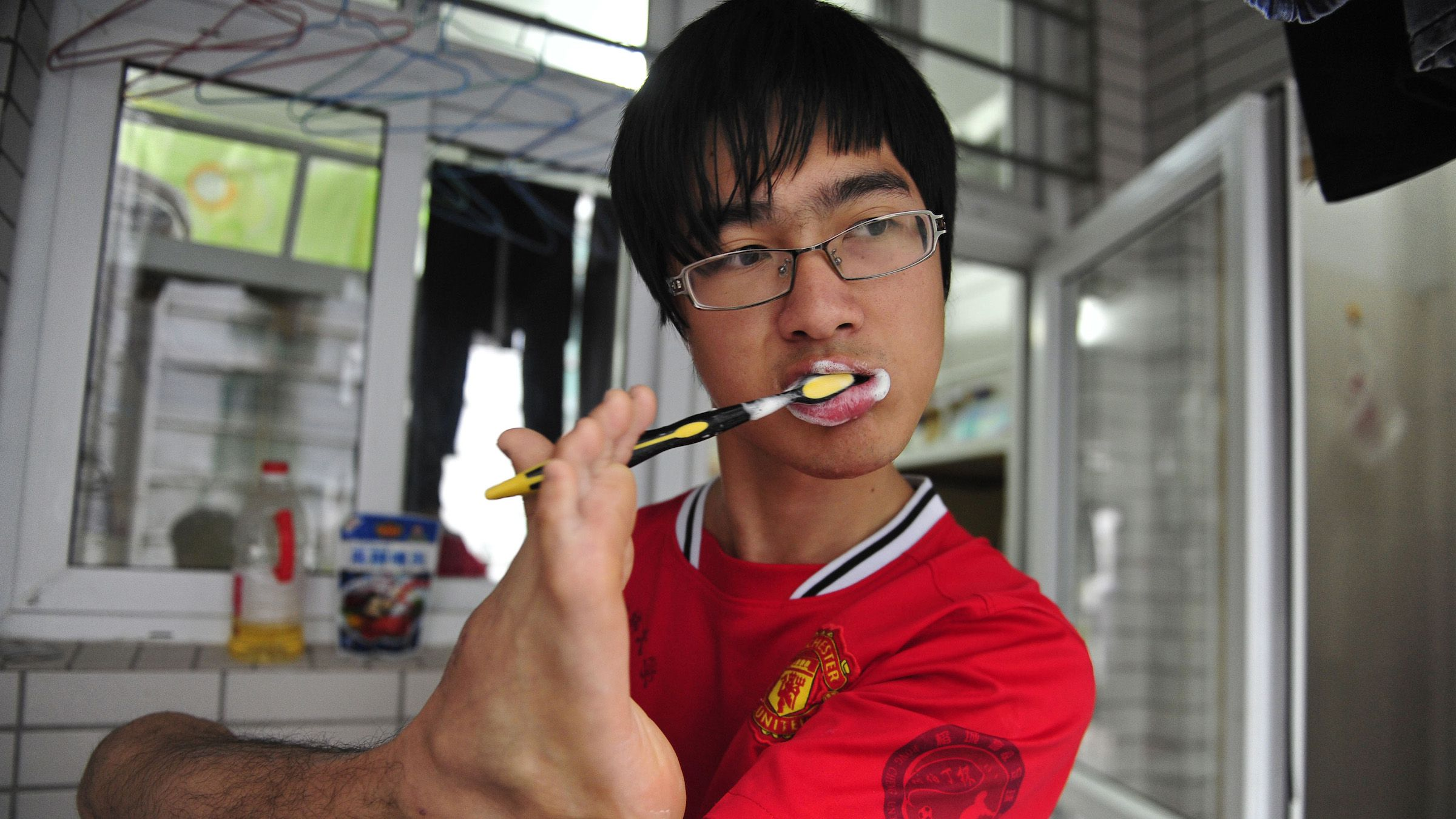 Fan Ling brushes his teeth with his foot