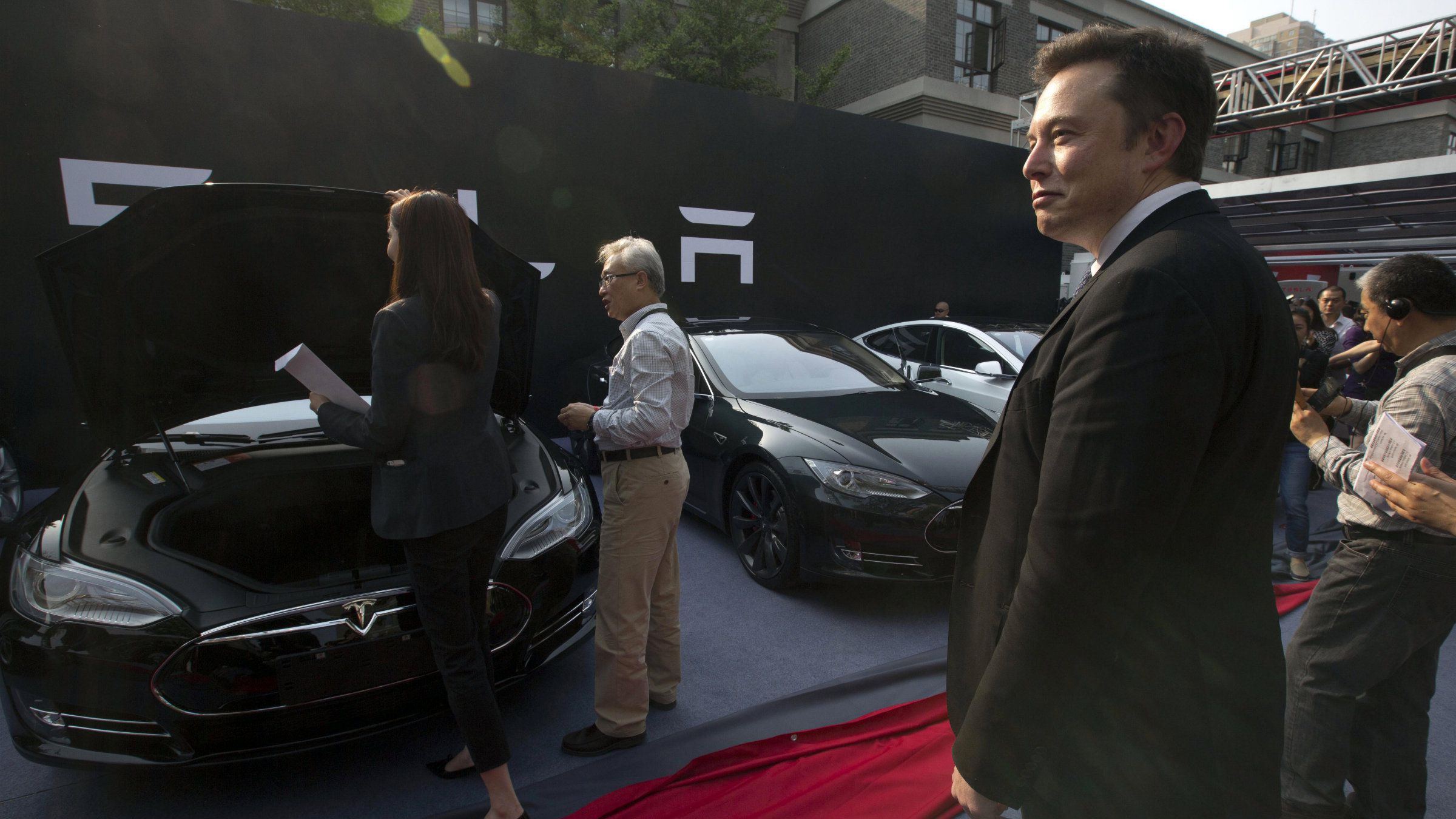 Tesla Motors CEO Elon Musk, right, looks on as a set of Tesla Model S sedans are delivered to its first customers in China at an event in Beijing, China, Tuesday, April 22, 2014.