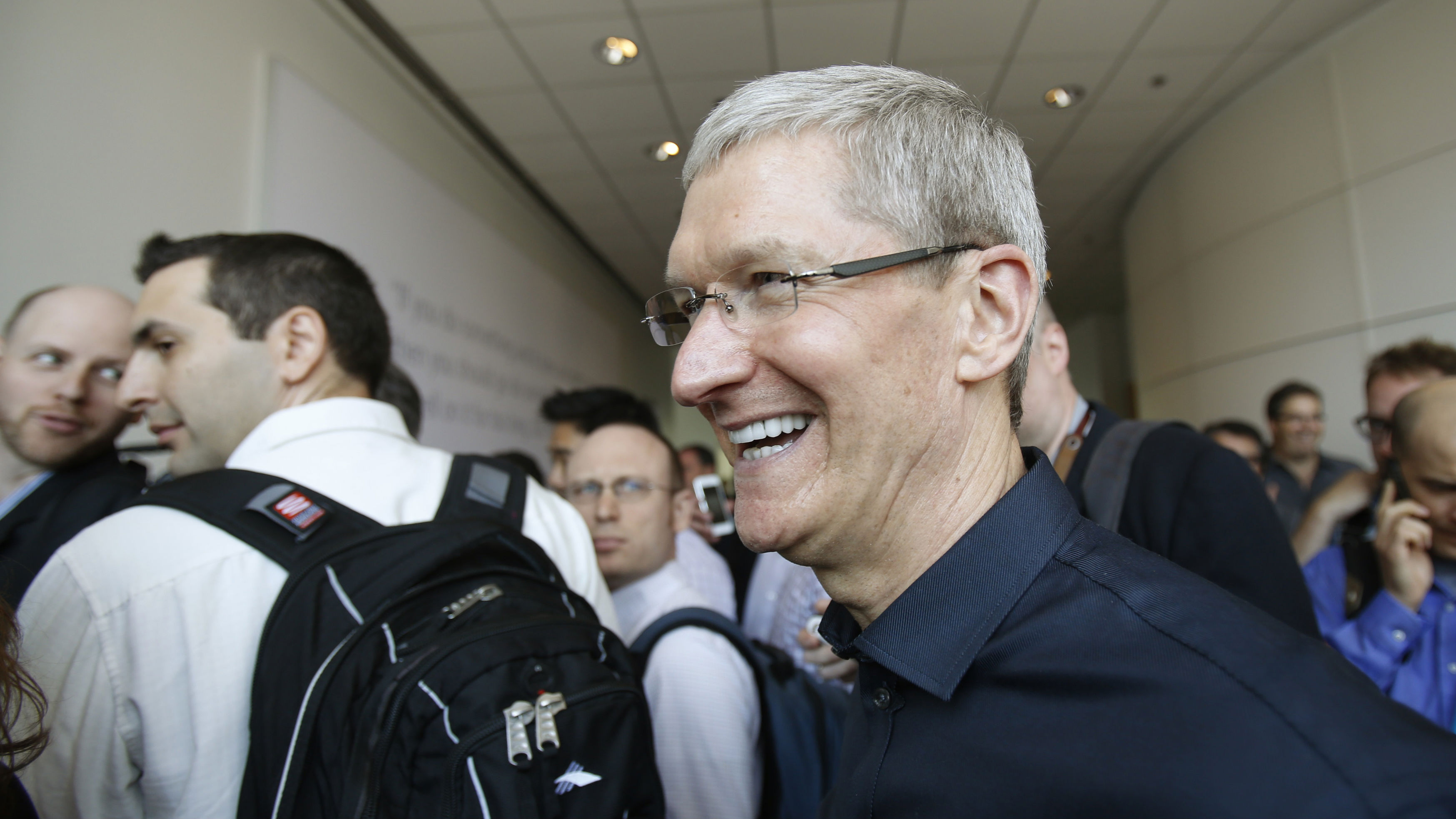 Apple Inc CEO Tim Cook walks into a display area of the company's new products after Apple Inc's media event in Cupertino, California September 10, 2013. REUTERS/Stephen Lam