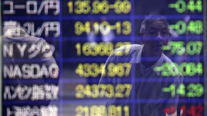 A man checking the stock prices is reflected on an electronic stock board of a securities firm in Tokyo Friday, Aug. 8, 2014. Asian stocks sank Friday as jitters over the crises in Iraq and Ukraine escalated but Chinese stocks rose after trade figures showed surprisingly strong growth in exports. In Japan, the 225-issue Nikkei Stock Average dived 454.00 points, or 2.98 percent, and finished at 14,778.37, hitting a two-month low. (AP Photo/Eugene Hoshiko)