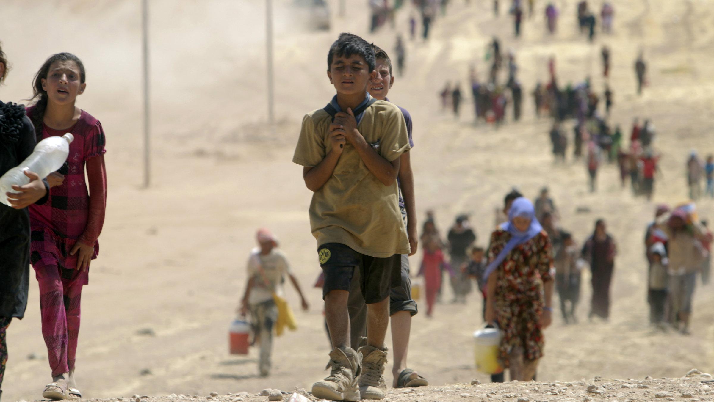 Yazidi people flee Sinjar toward the Syrian border on Aug. 10, 2014.