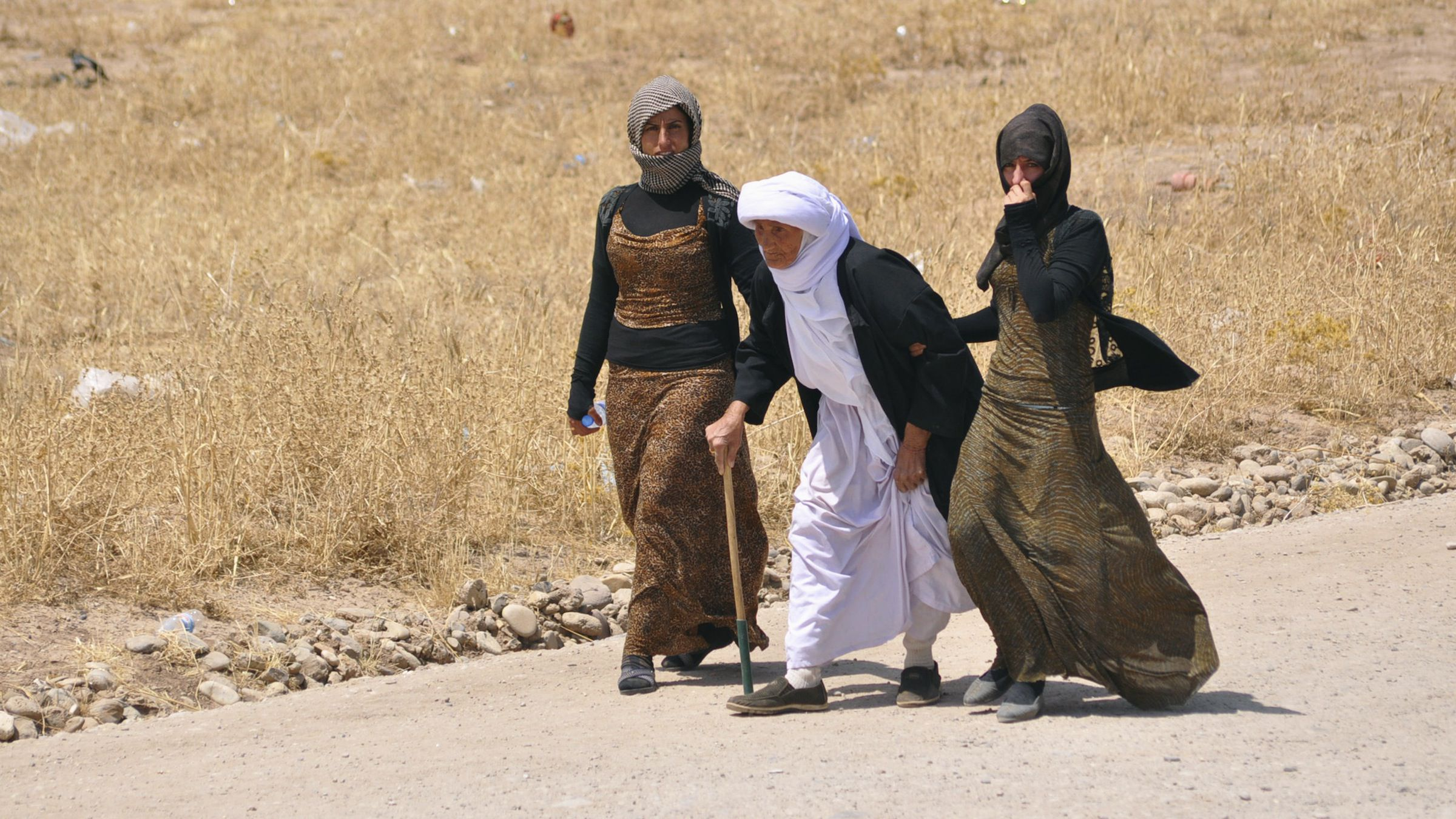 Displaced families from the minority Yazidi sect, fleeing the violence, walk on the outskirts of Sinjar, west of Mosul, August 5, 2014.  Tens of thousands fled the weekend assault on Sinjar and are now surrounded, according to witnesses and the United Nations, after the Sunni militants inflicted a humiliating defeat on Kurdish forces who had held towns in the area for years. Picture taken August 5, 2014. REUTERS/Stringer (IRAQ - Tags: CIVIL UNREST POLITICS CONFLICT RELIGION TPX IMAGES OF THE DAY) - RTR41ERA