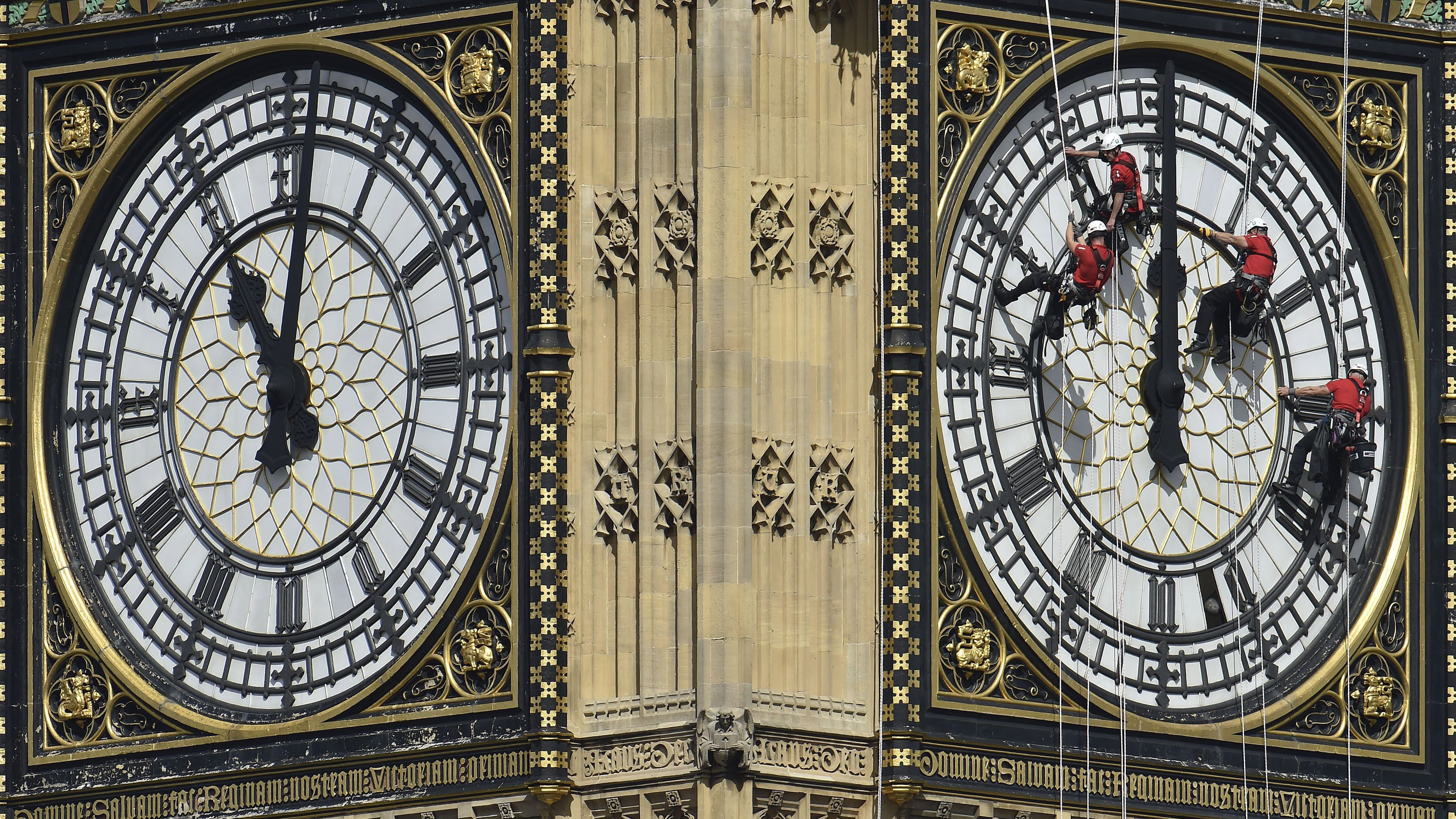 Cleaners abseil down one of the faces of Big Ben, to clean and polish the clock face, above the Houses of Parliament, in central London August 19, 2014. A week has been set aside for the cleaning of what is officially known as the Great Clock, which is set in the Elizabeth Tower. REUTERS/Toby Melville