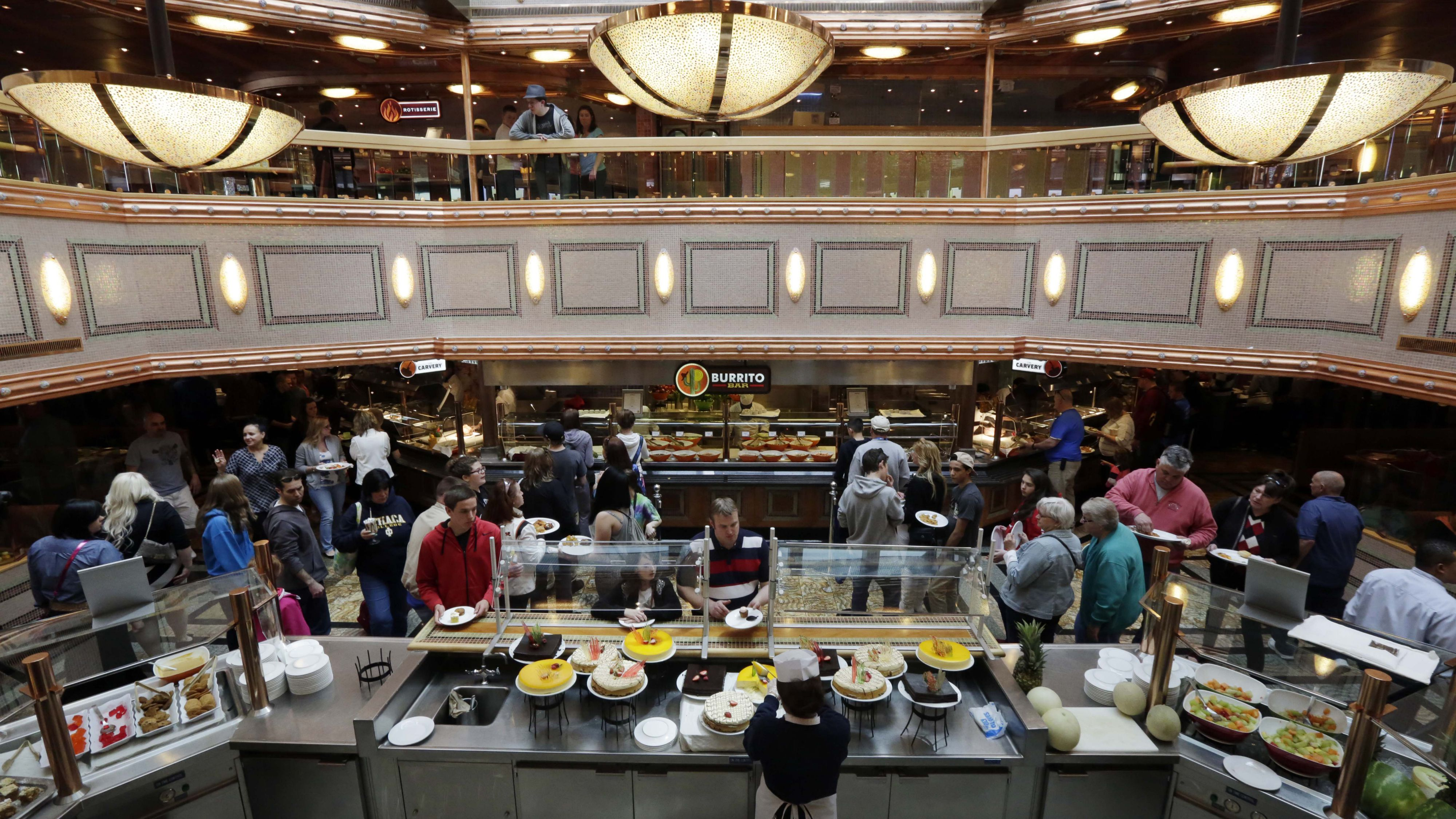 In this April 18, 2014 photo, passengers get lunch at the Burrito Bar, Carvery, and dessert bar of the Grand Buffet, aboard the Carnival Splendor cruise ship, in New York. Carnival Cruise CEO Arnold Donald is taking over a troubled, family-run business and trying to convert the world's largest cruise line into a profitable venture. (AP Photo/Richard Drew)