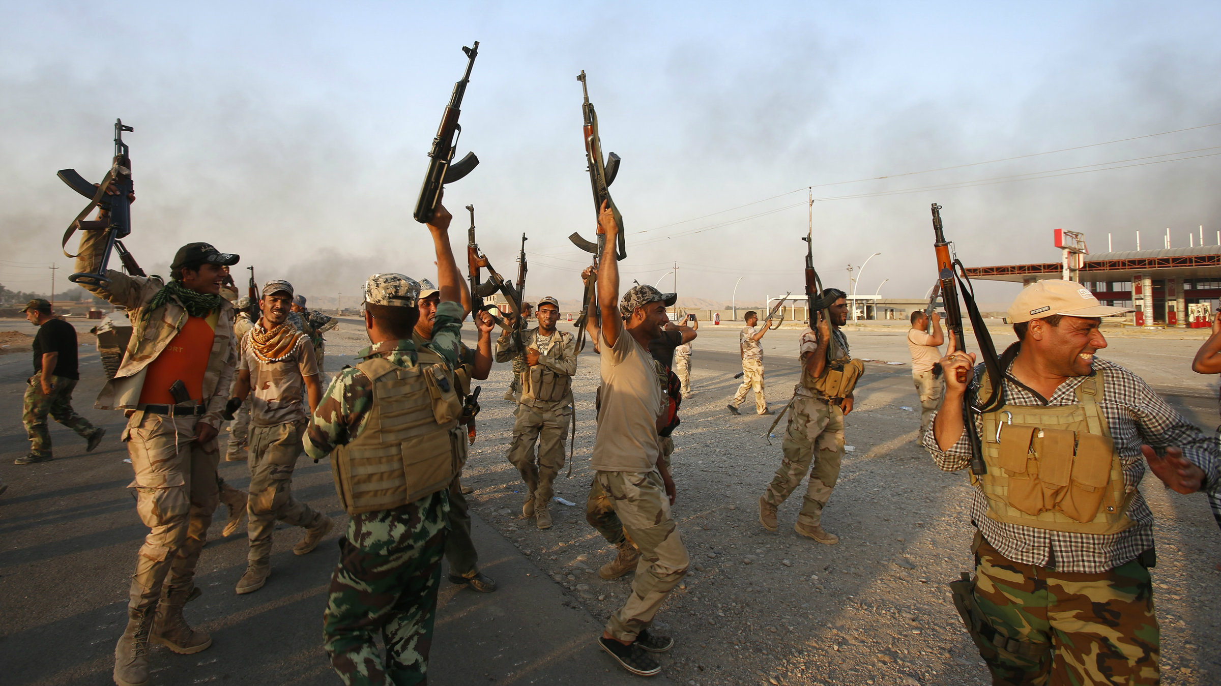 Iraqi Shiite militia fighters fire their weapons as they celebrate breaking a long siege of Amerli by Islamic State militants, September 1, 2014. REUTERS/Youssef Boudlal (