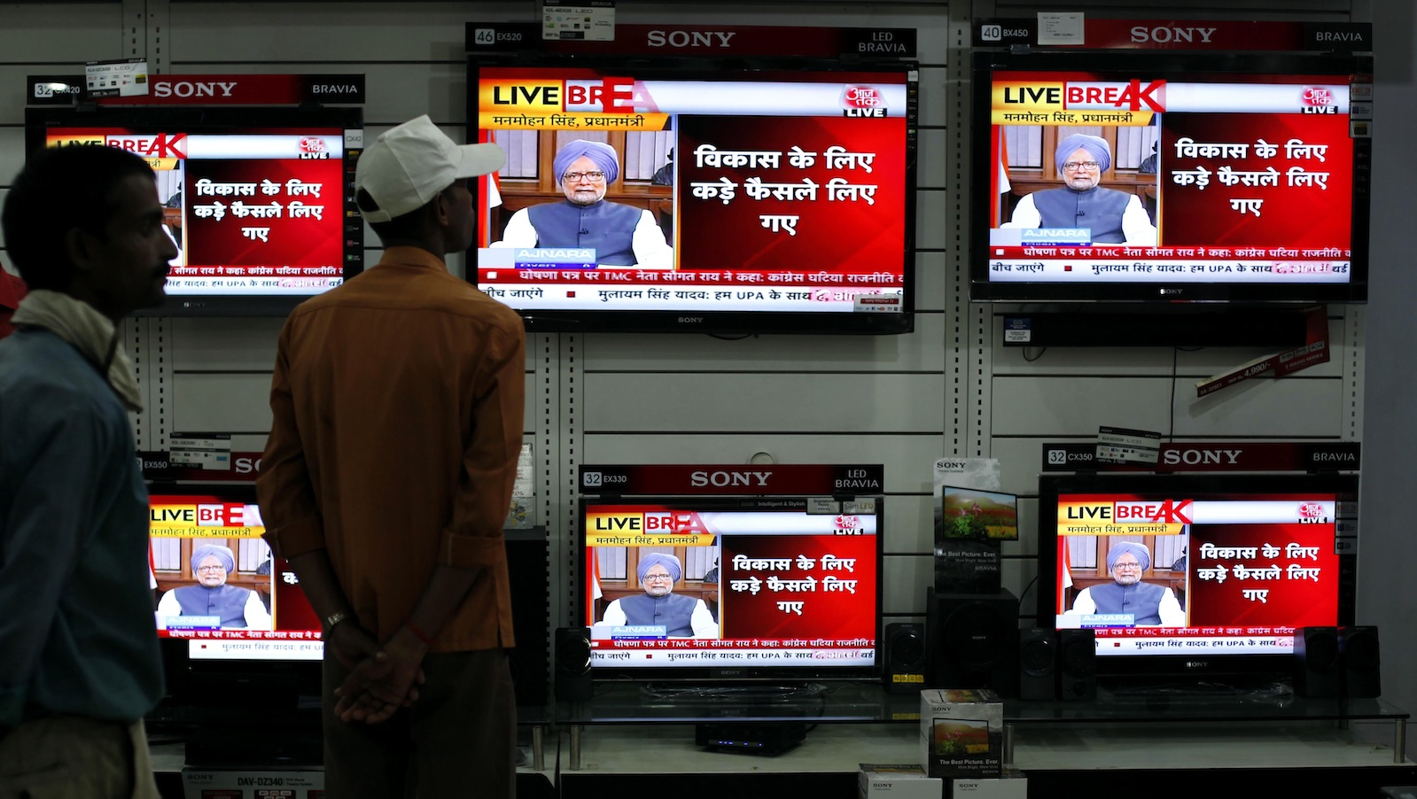 Indians watch Prime Minister Manmohan Singh address the nation on television, at a television showroom in Allahabad, India, Friday, Sept. 21, 2012. Singh's address to the nation came after the Trinamool Congress party pulled out of the ruling coalition protesting the decision to allow foreign retail chains to come into the country. (AP Photo/Rajesh Kumar Singh)